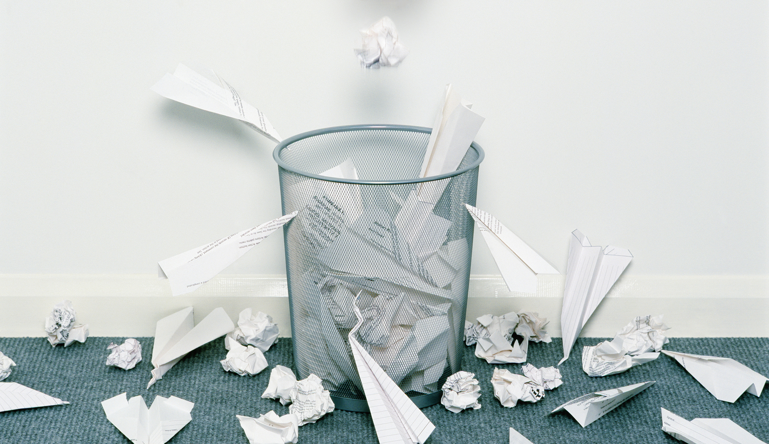Man dropping crumpled paper in bin surrounded with paper aeroplanes