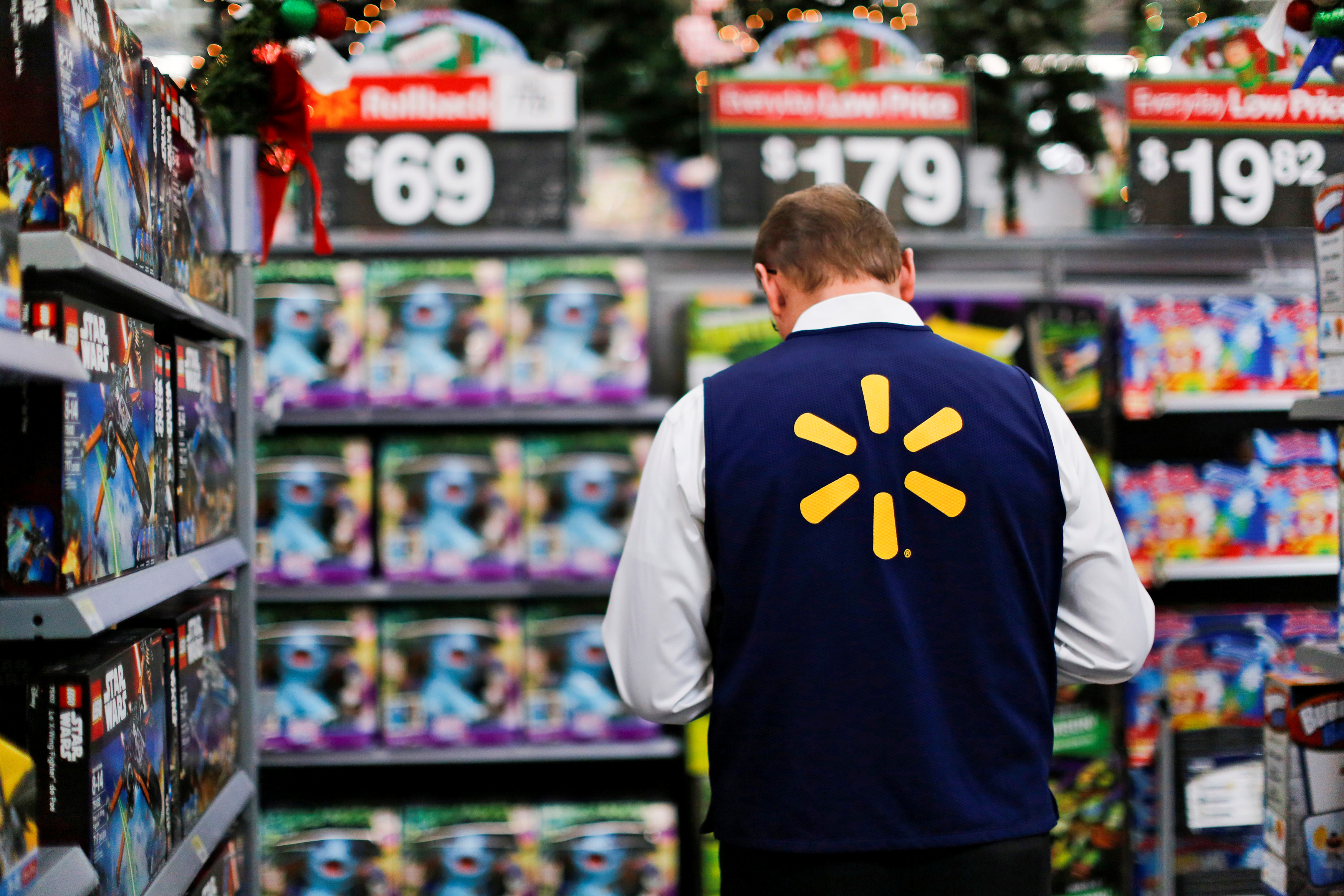 A Walmart worker organises products for Christmas season at a Walmart store in Teterboro