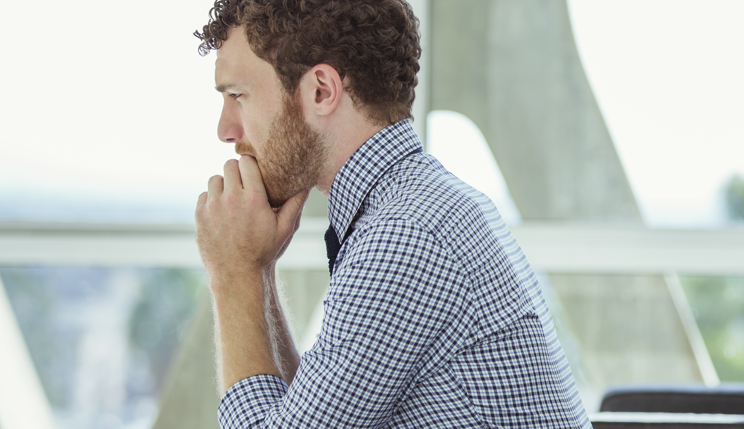 Pensive businessman sitting in office lobby
