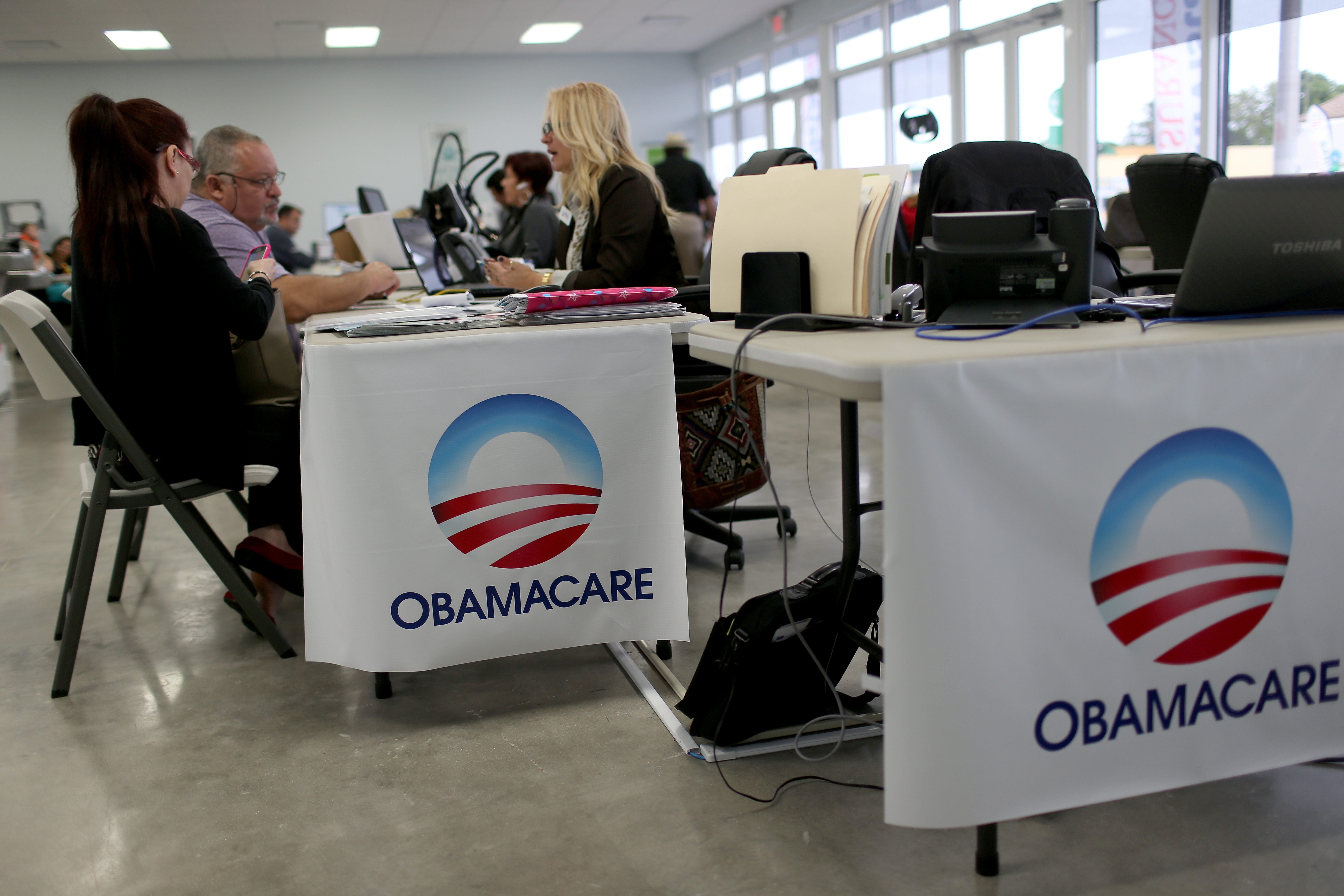 Aymara Marchante (L) and Wiktor Garcia sit with Maria Elena Santa Coloma, as they sign up for the Affordable Care Act, also known as Obamacare, before the February 15th deadline on February 5, 2015 in Miami, Florida.