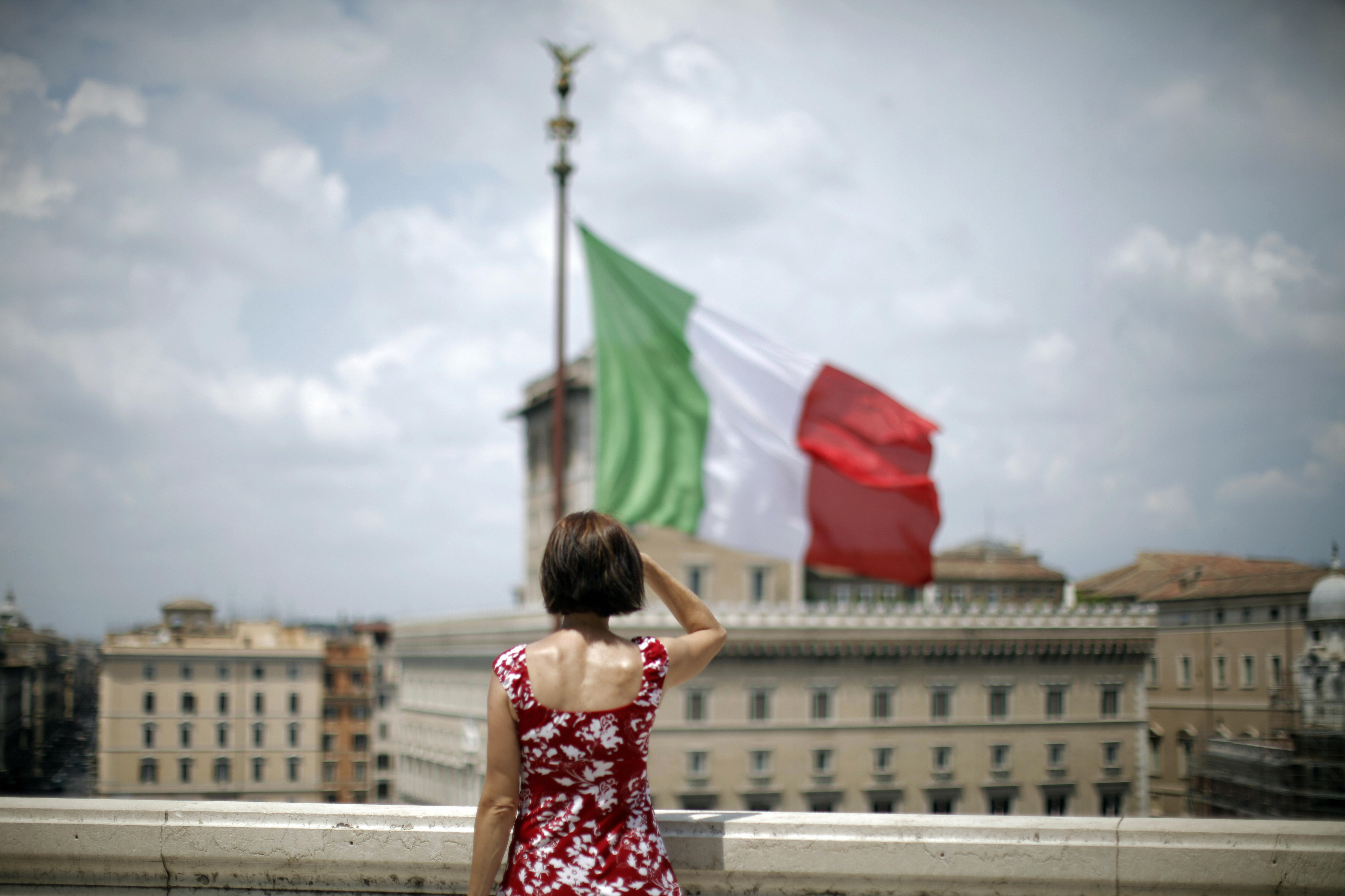 A woman stands in front of a waving Ital