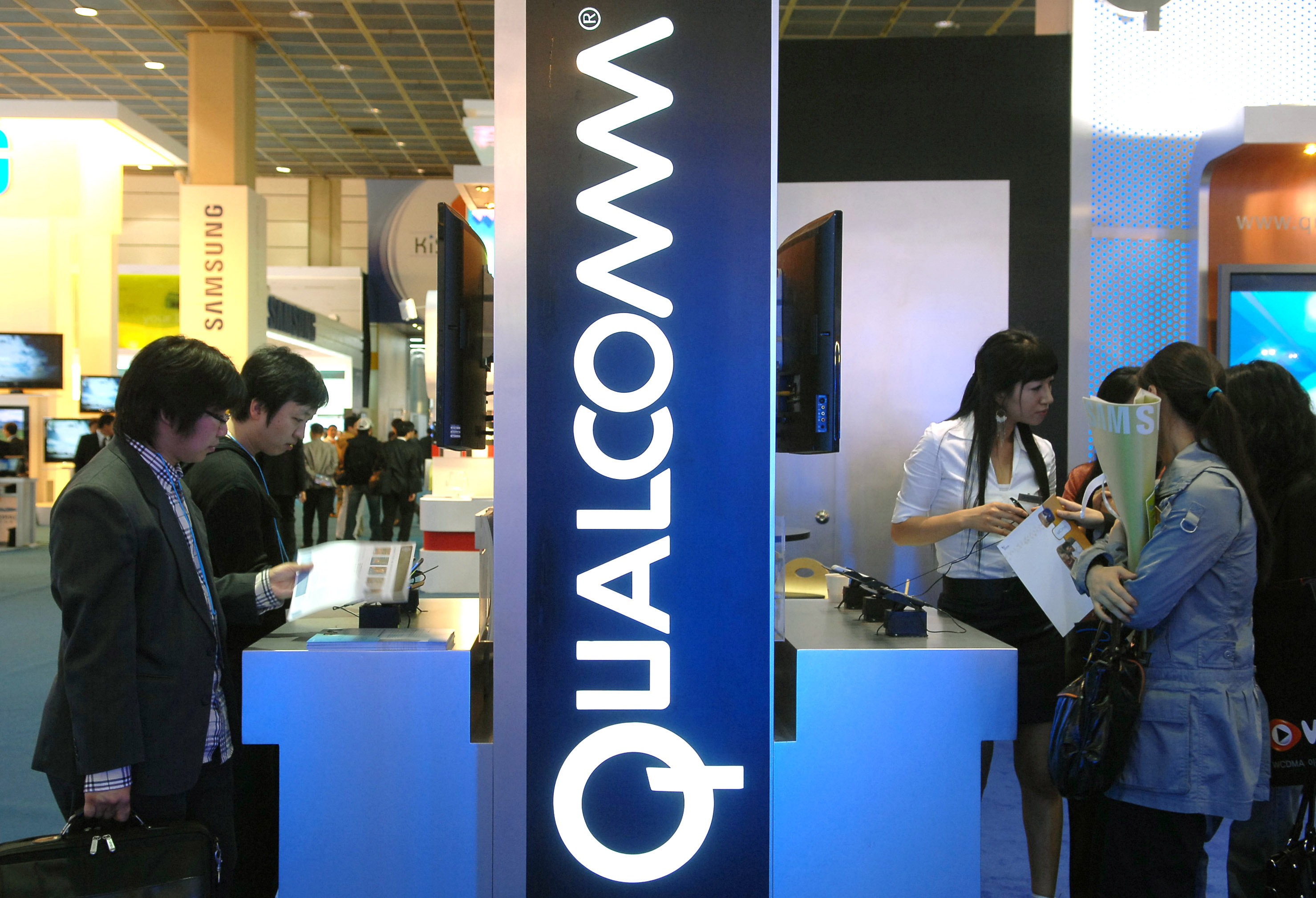Visitors look around a Qualcomm display at the Korea IT Show