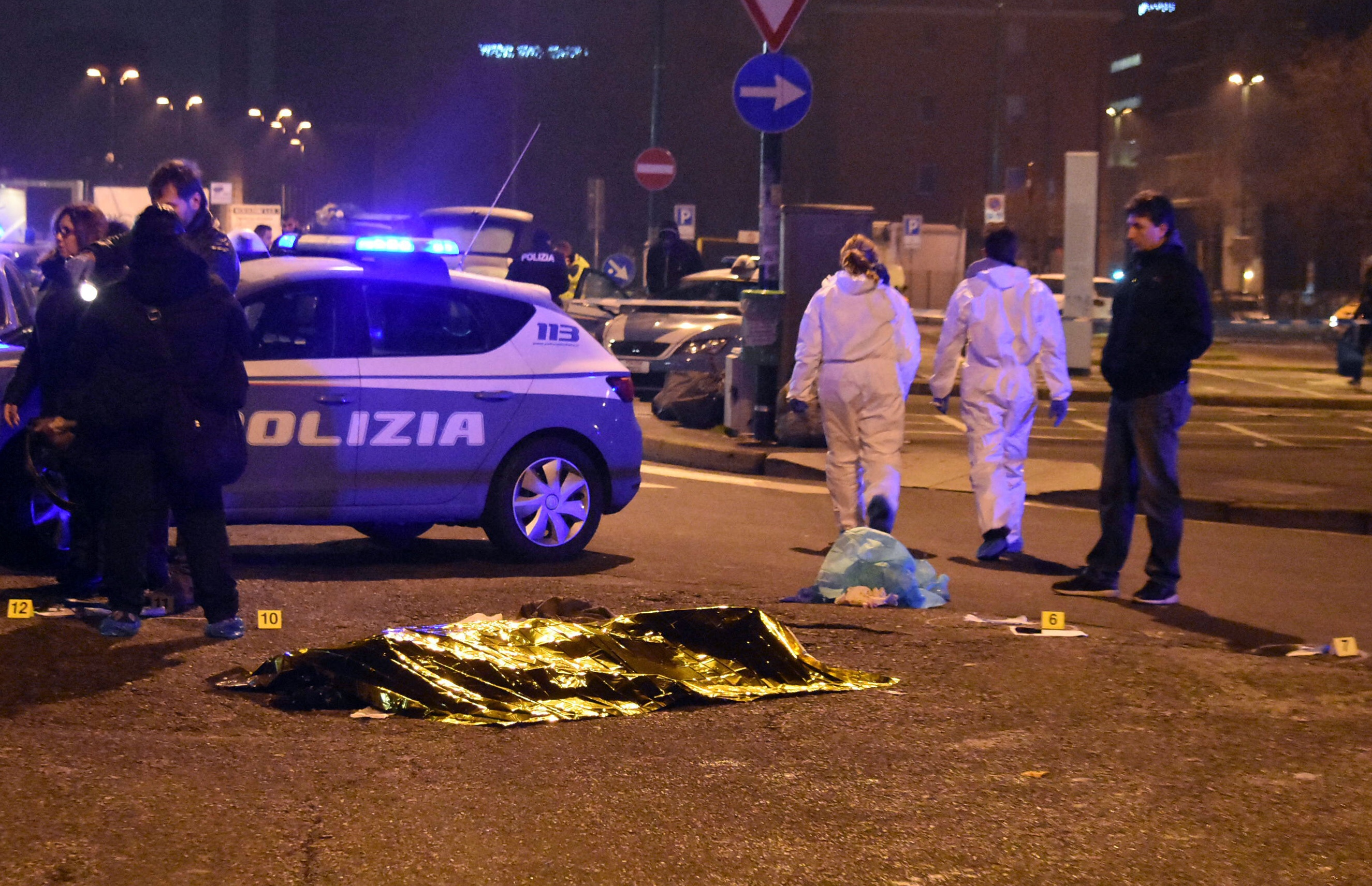 A body is covered with a thermic blanket after a shootout between police and a man near a train station in Milan's Sesto San Giovanni neighborhood, Italy, early Friday, Dec. 23, 2016