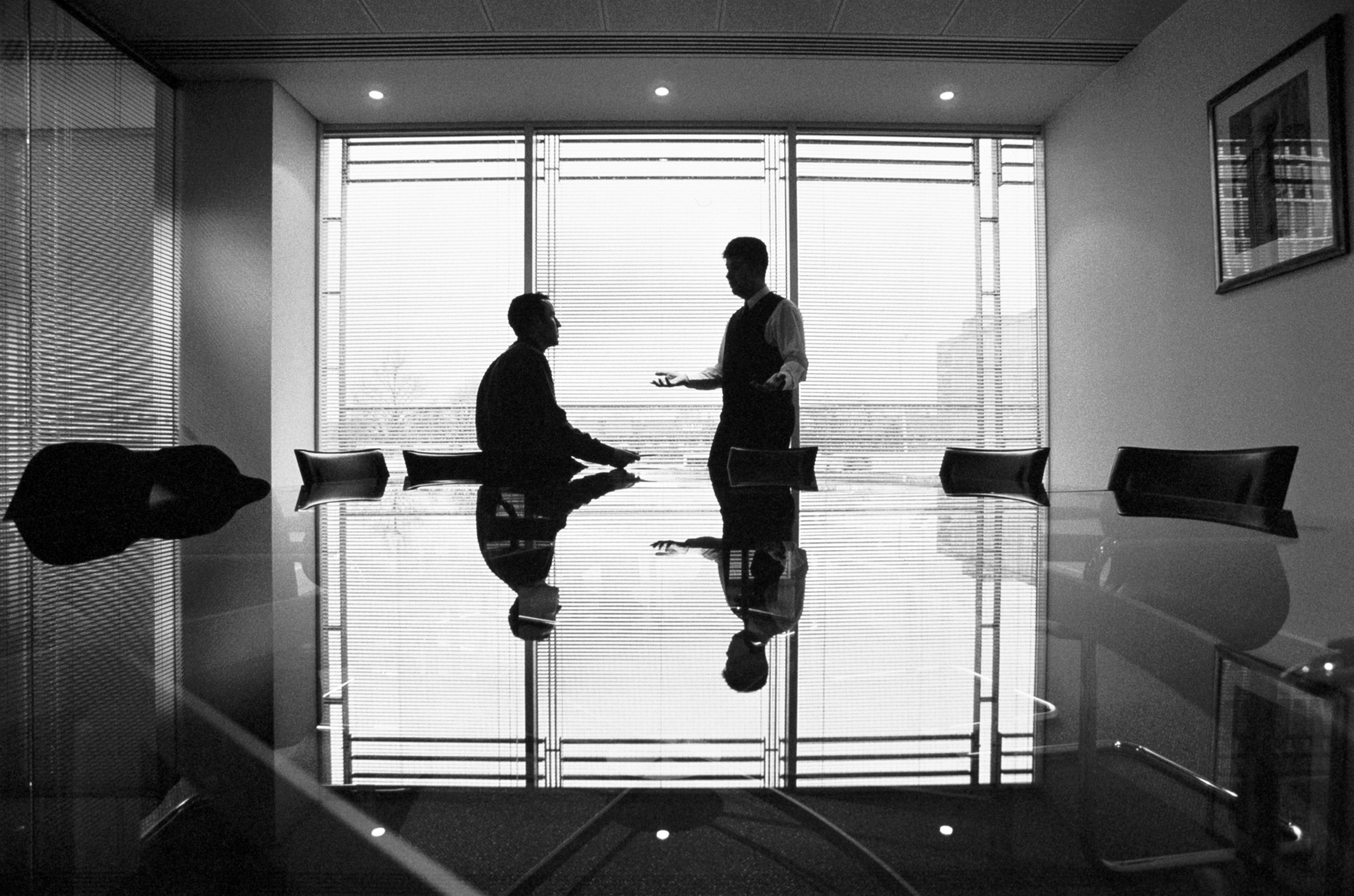 Two businessmen talking in conference room, silhouette (B&W)