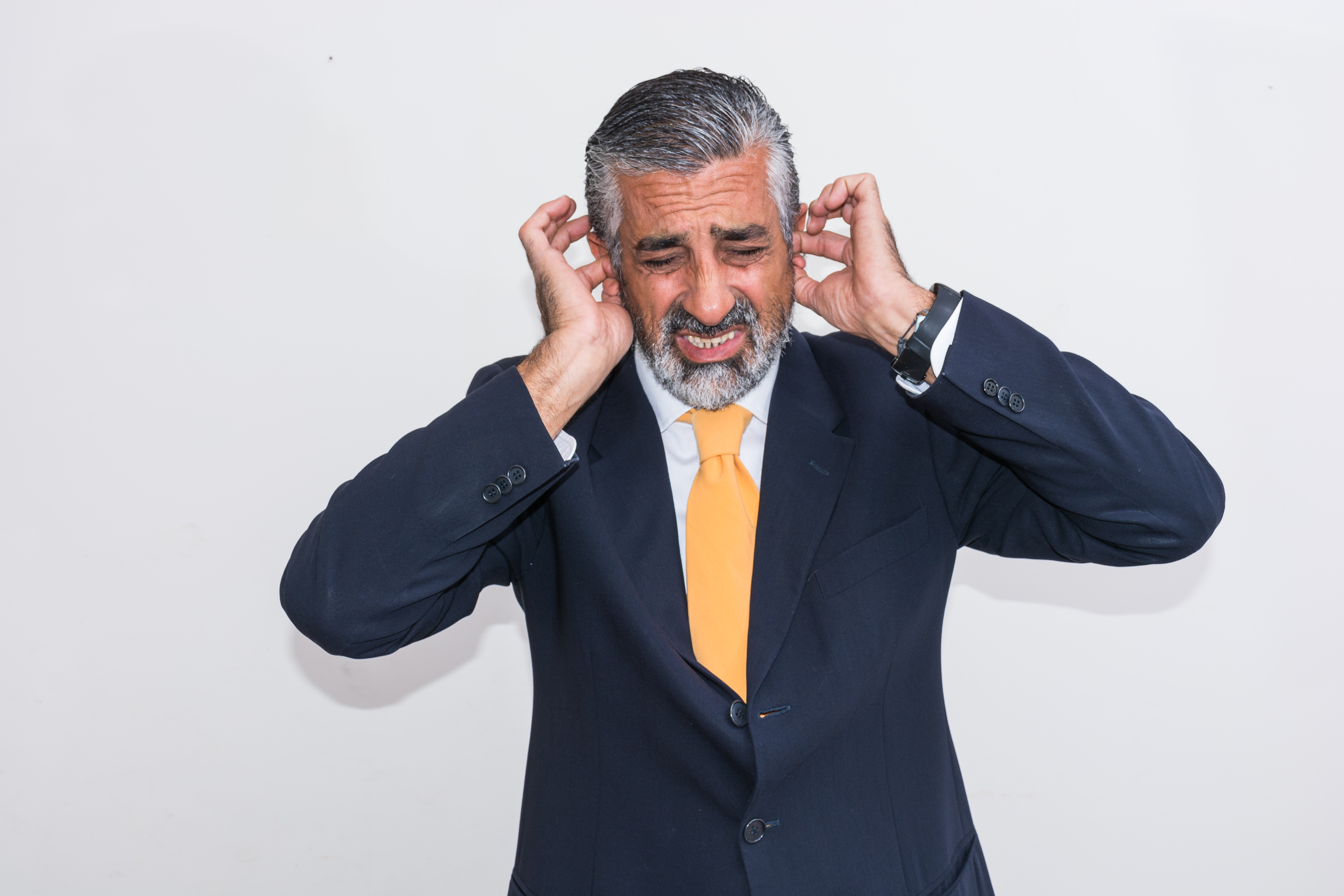 Businessman With Hands Covering Ears Against Wall