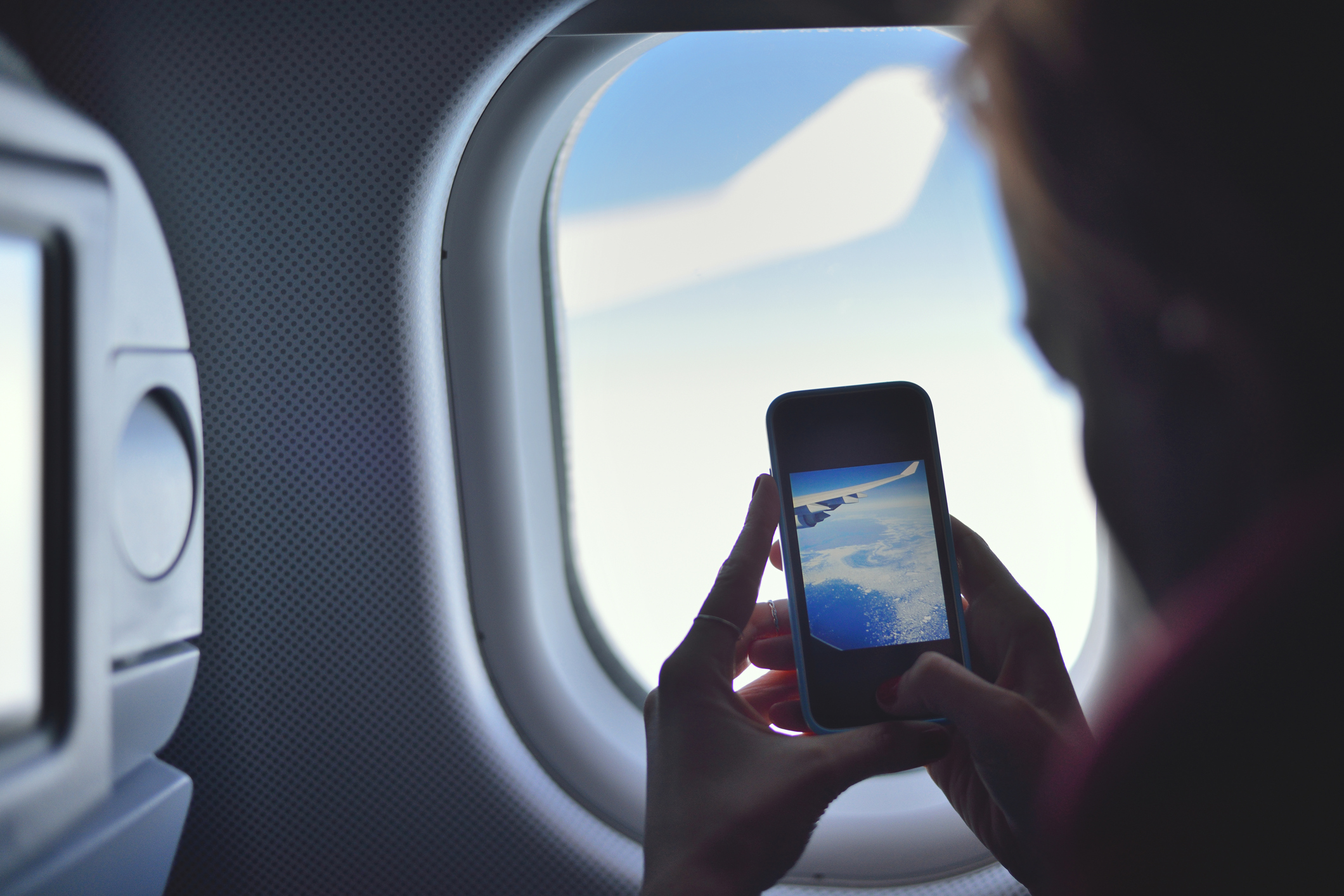Young woman taking a picture on an airplane