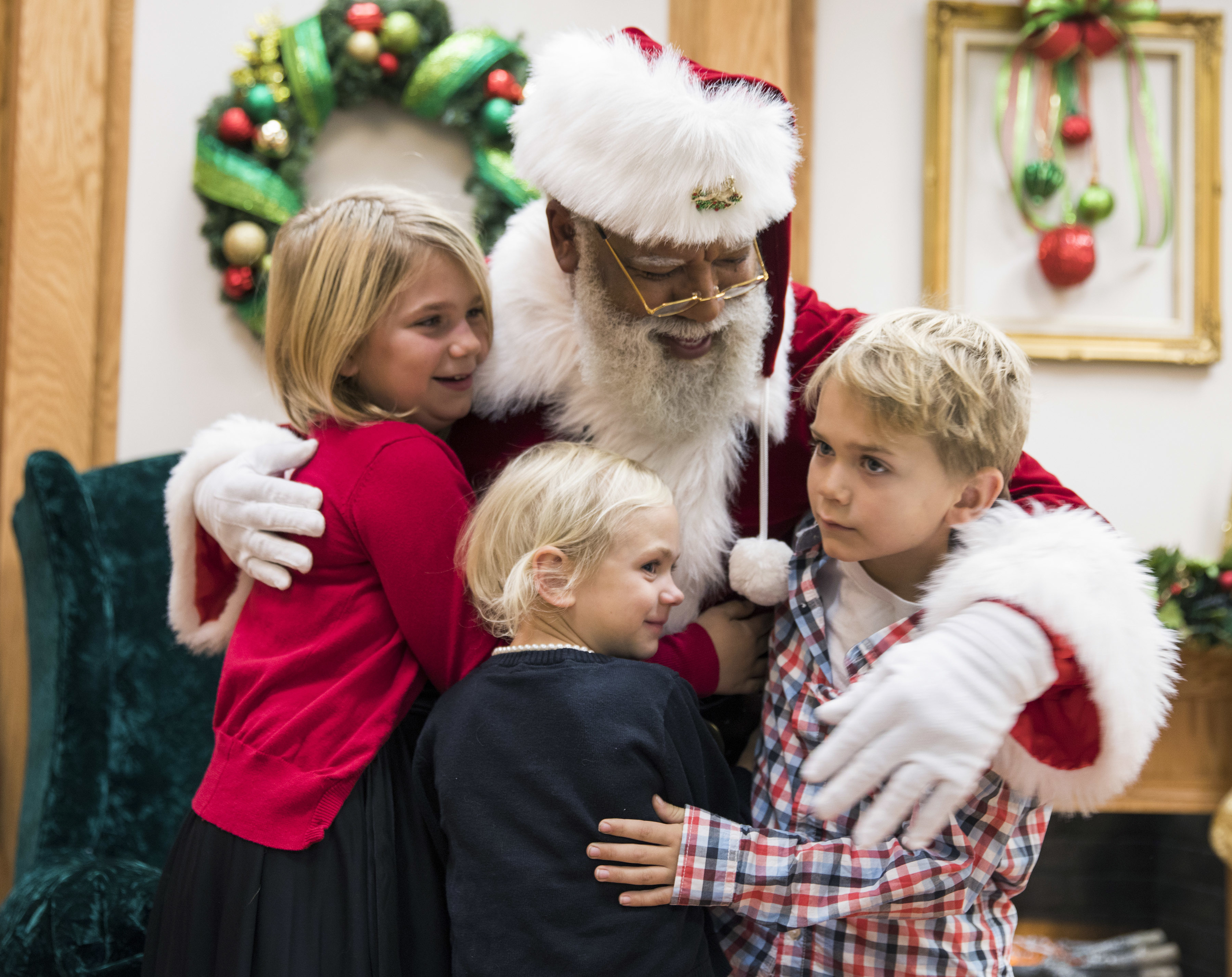 Larry Jefferson, playing the role of Santa, gets a hug from Olivia Major, left, her sister Mallory and brother Preston, of Blaine, at the Santa Experience at Mall of America in Bloomington, Minn.