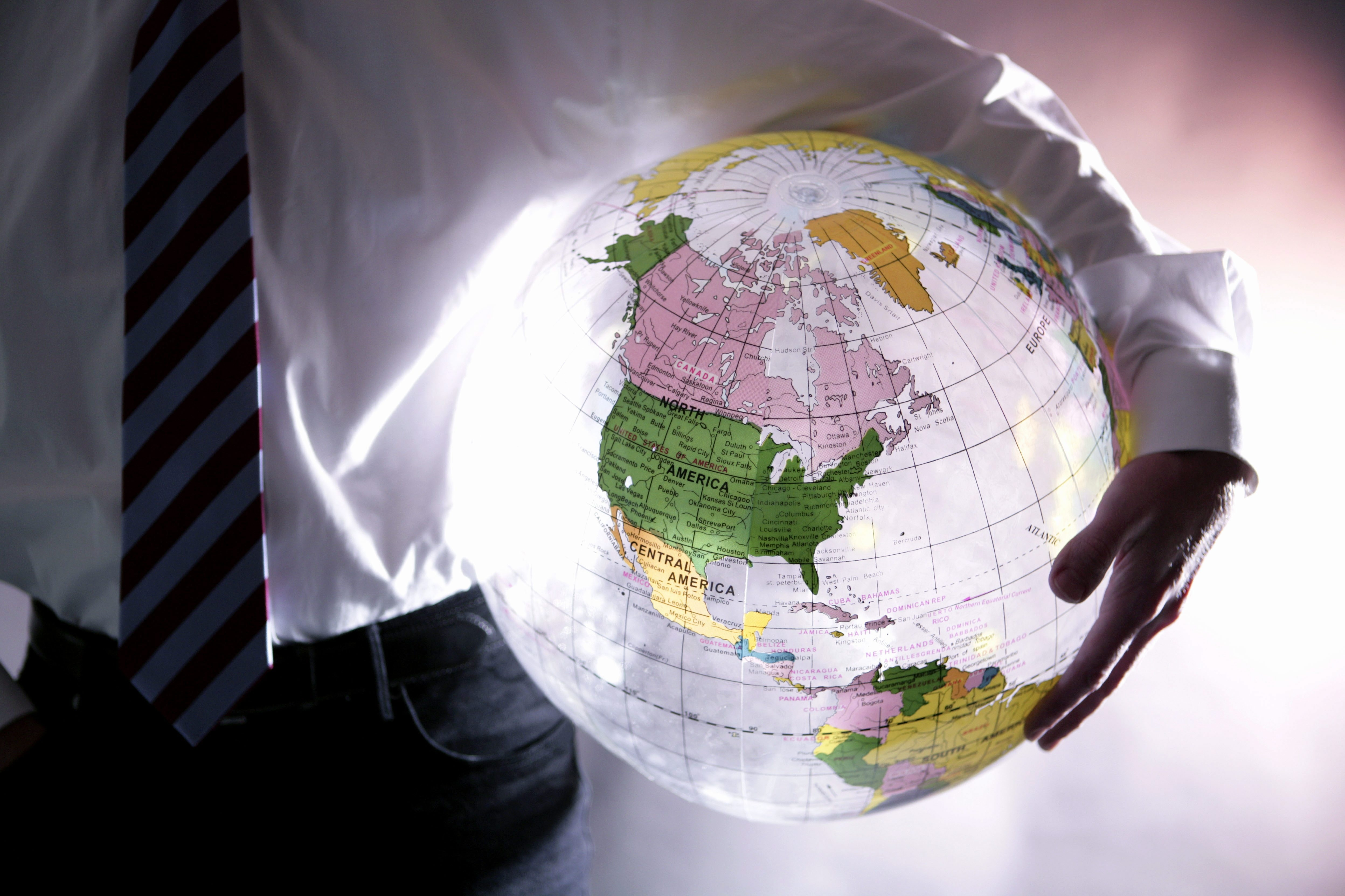Globalization - manager with a globe under his arm.