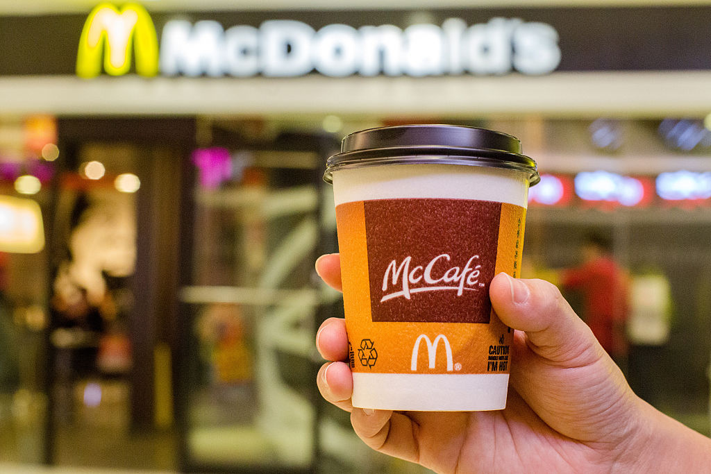 BEIJING, CHINA - 2015/01/28: A customer holds a cup of Coffee served by McCafe out of a McDonald's restaurant.  In the 2014 fiscal figures released on January 23, 1%  drop in global sales in 2014 highlighted the challenges McDonald's faced. Especially, weak economy in Russia and supplier issue In China drives down McDonald's revenue growth in 2014. (Photo by Zhang Peng/LightRocket via Getty Images)