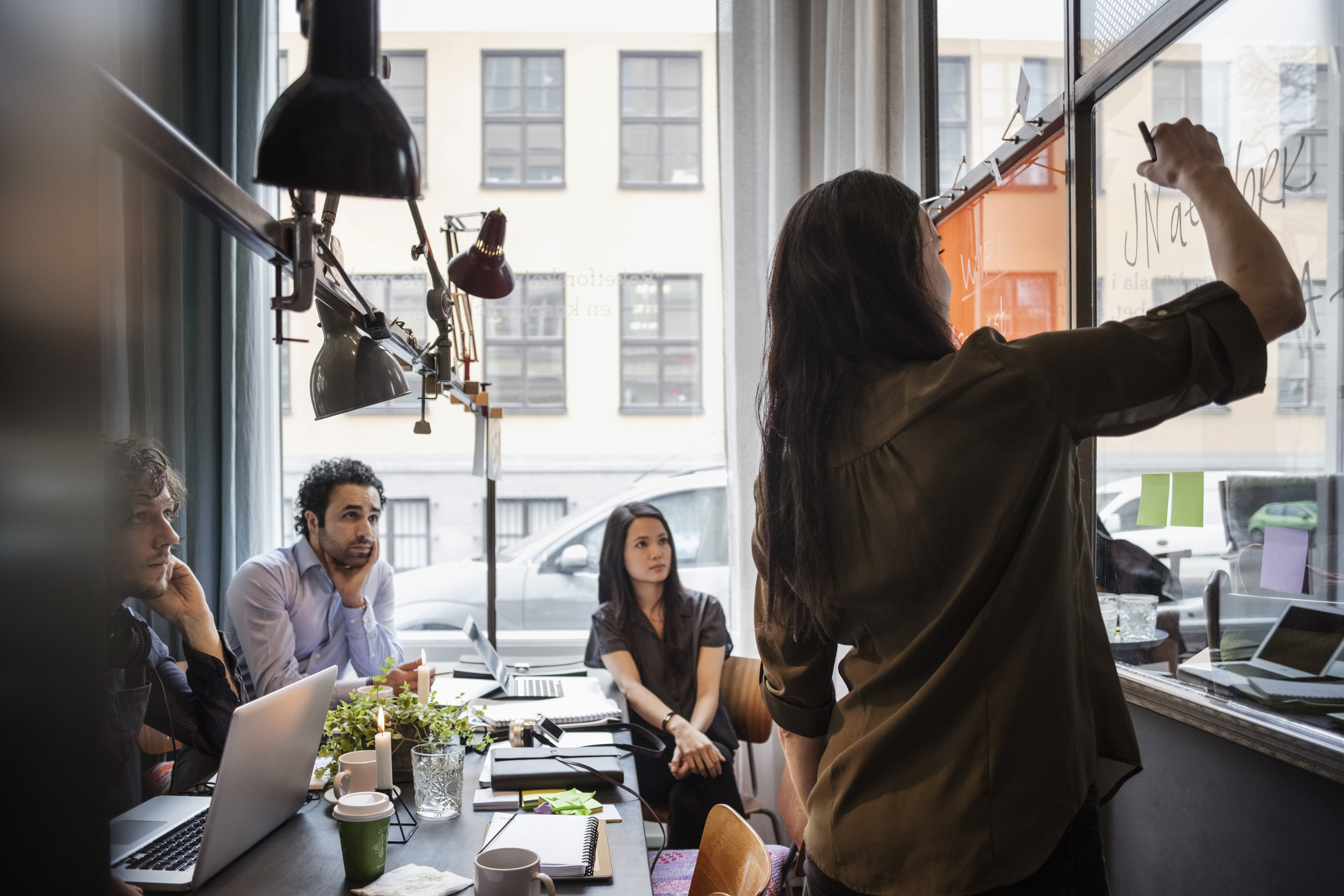 Creative business people looking at female coworker writing on glass in office