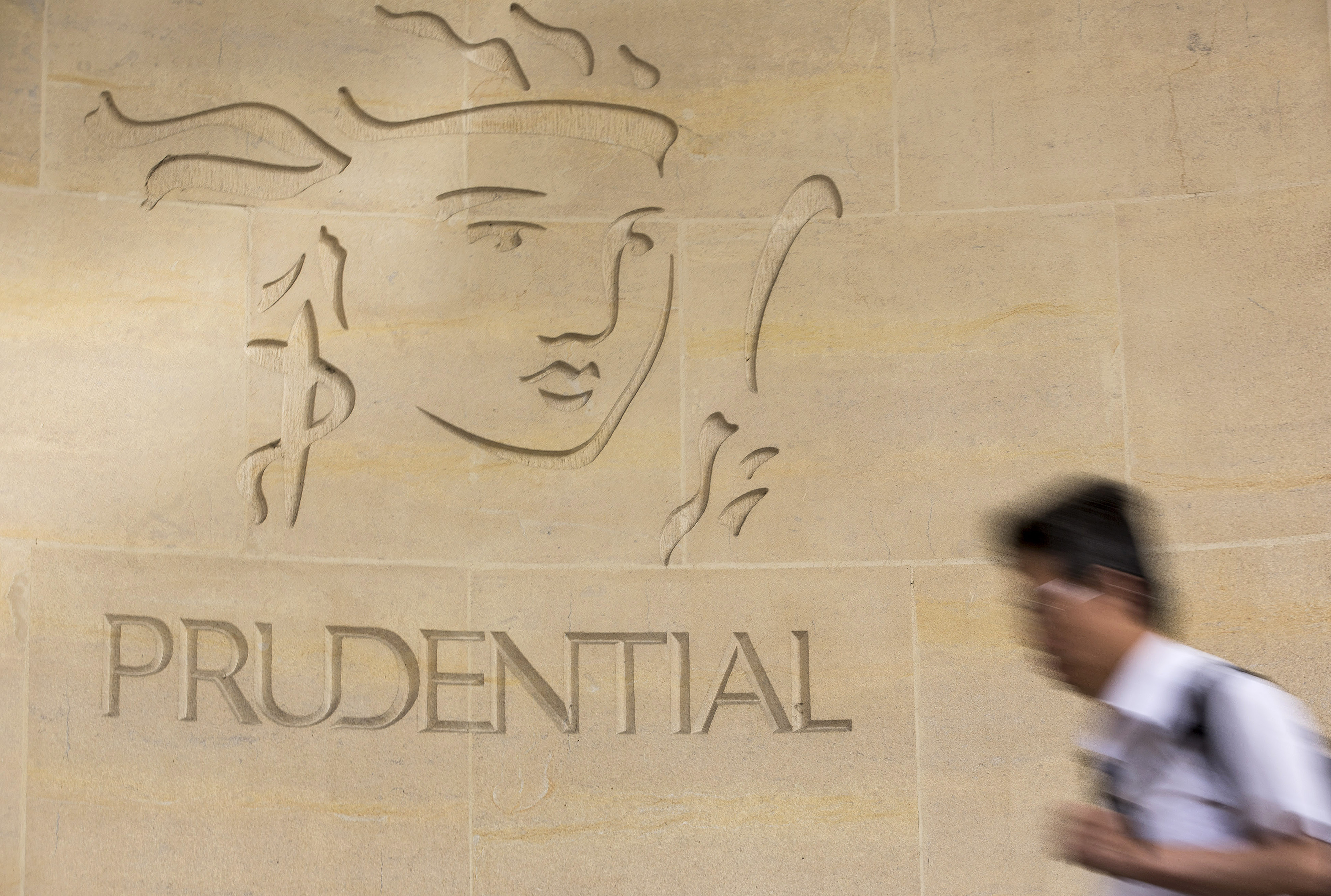 A pedestrian passes a logo outside Prudential Plc's headquarters in London, U.K., on Monday, Aug. 12, 2013.