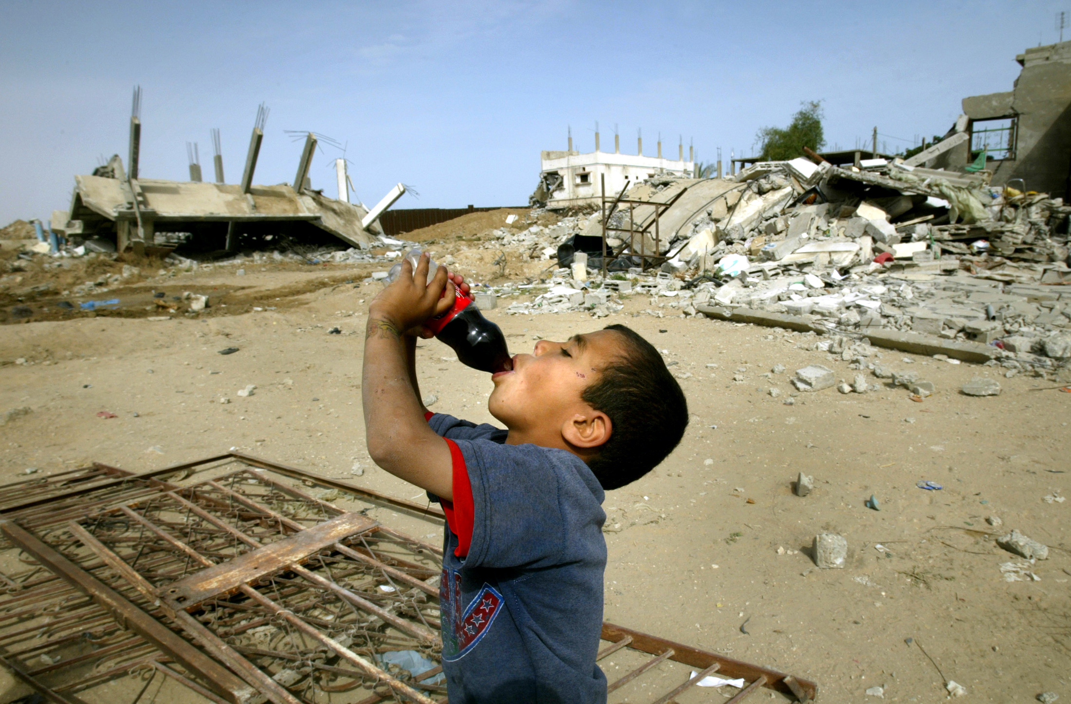 PALESTINIAN BOY DRINKS COCA-COLA NEXT TO HOUSES DESTROYED AT RAFAH REFUGEE CAMP.