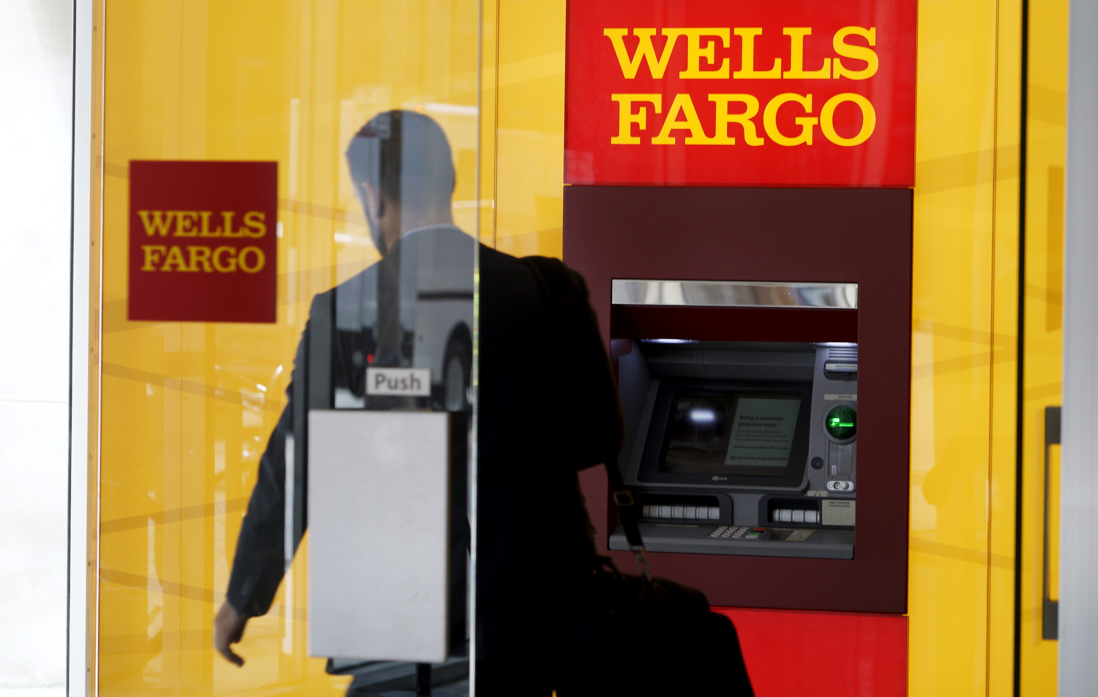 A man walks by a bank machine at the Wells Fargo & Co. bank in downtown Denver