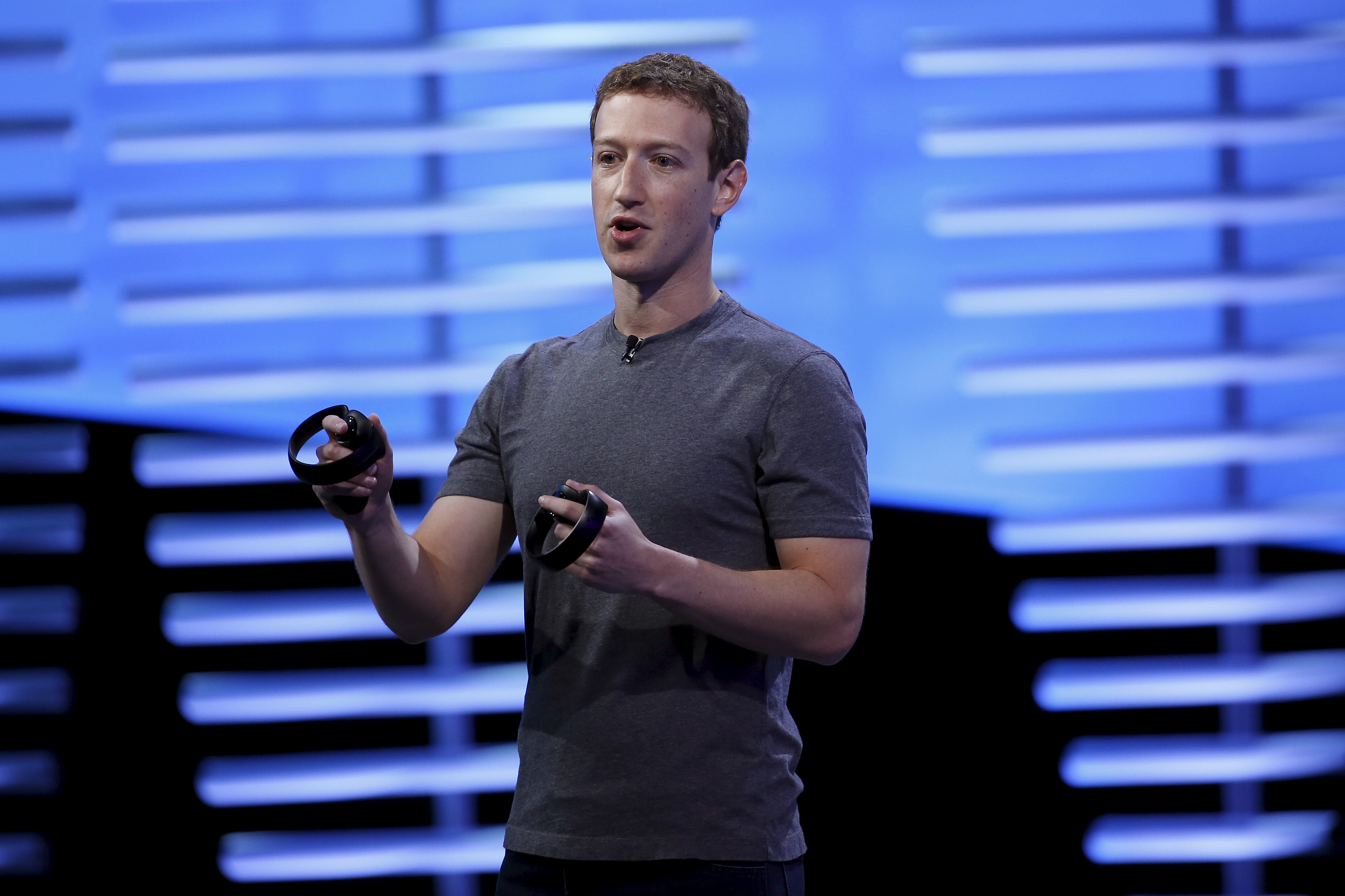 Facebook CEO Mark Zuckerberg holds a pair of the touch controllers for the Oculus Rift virtual reality headsets during the Facebook F8 conference in San Francisco, California