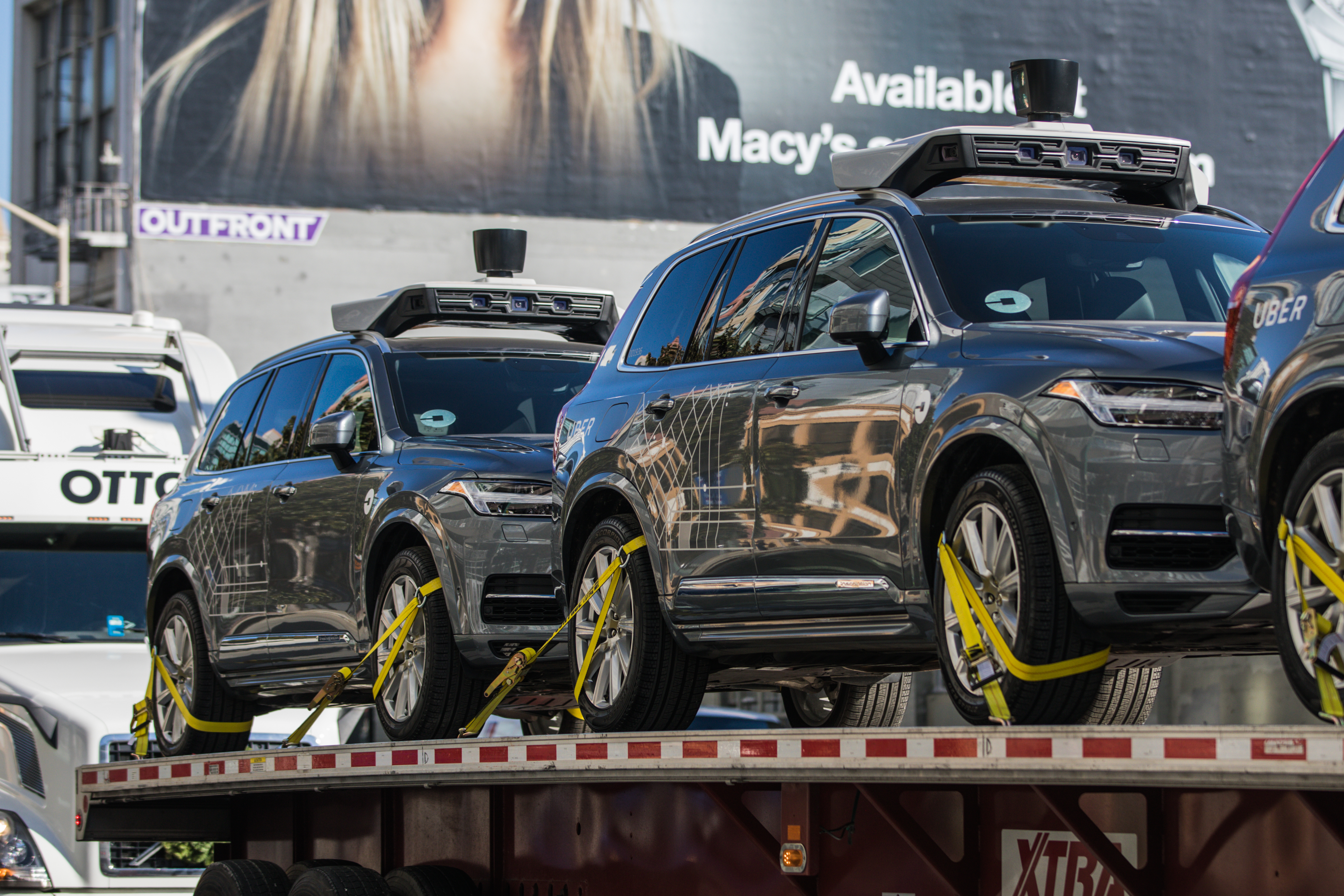 Uber's self-driving Volvo cars being loaded on an Otto truck.