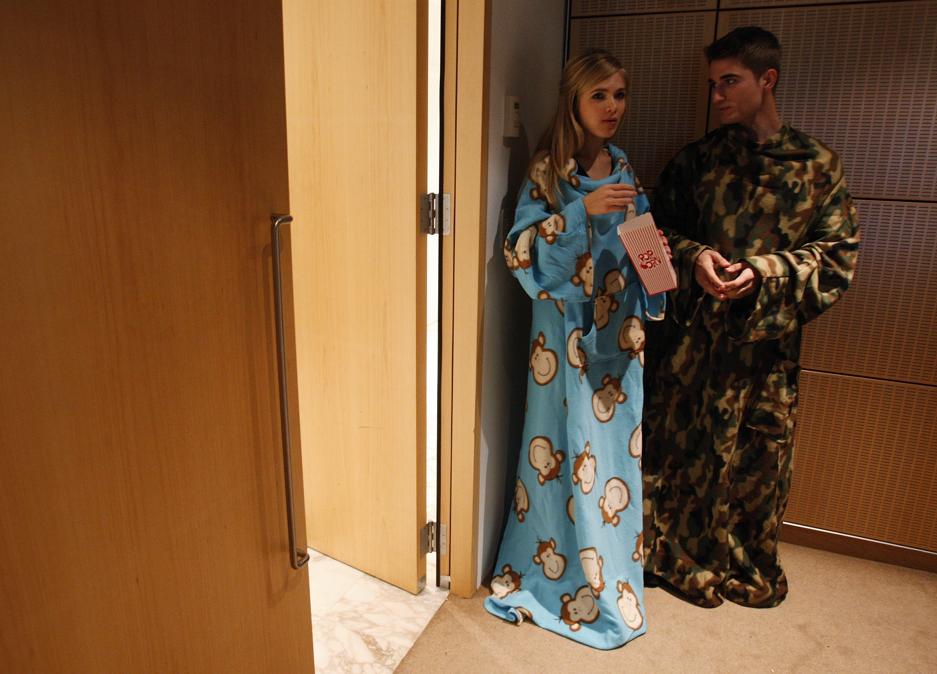 Models wearing snuggies eat popcorn after the Snuggie Choice Film Awards in New York