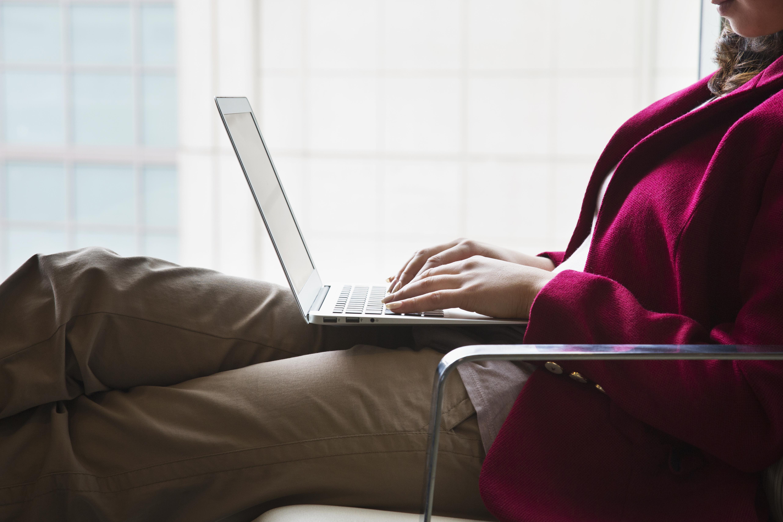 Hispanic woman using laptop in chair