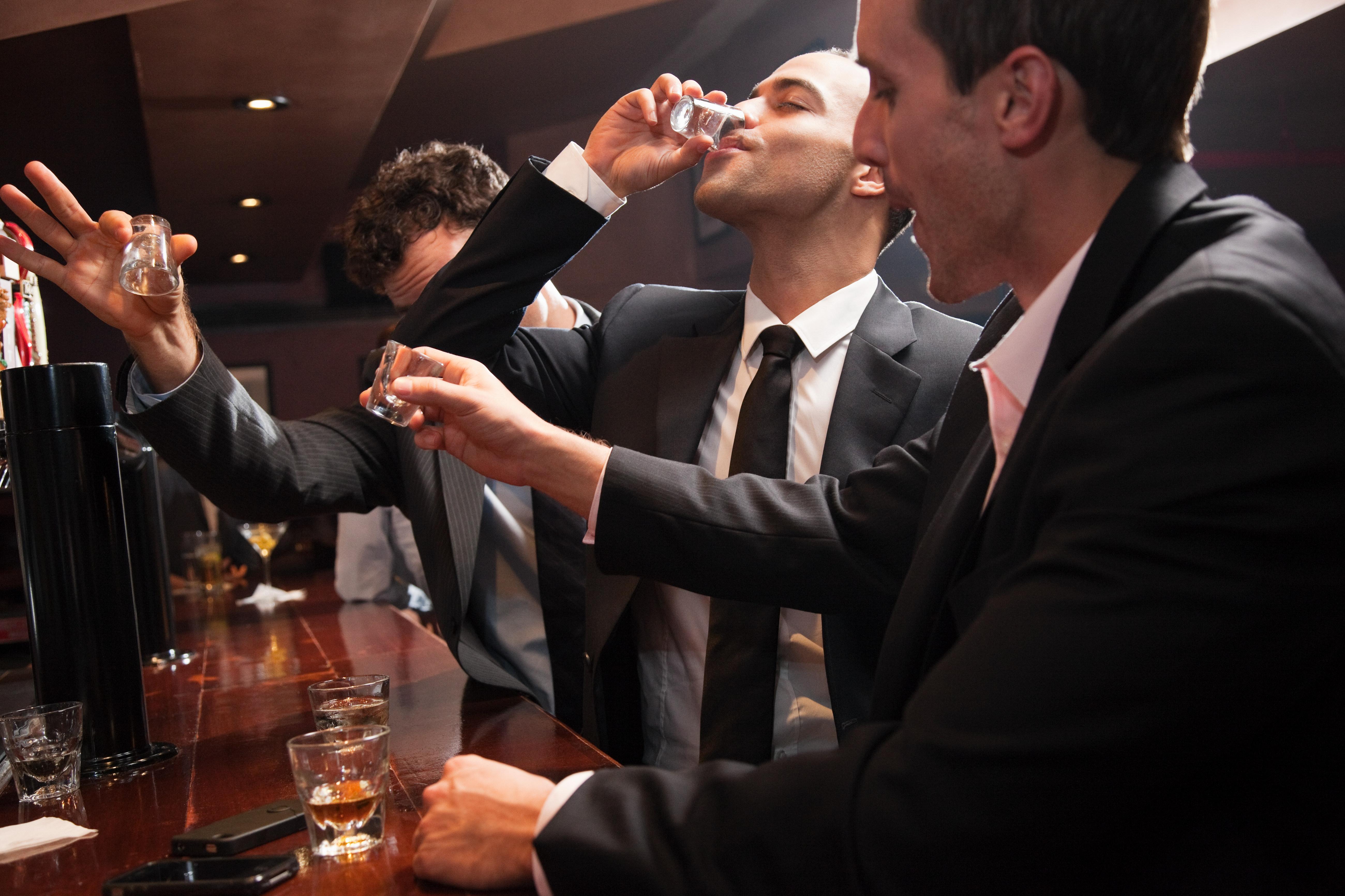 Businessmen drinking shots in bar