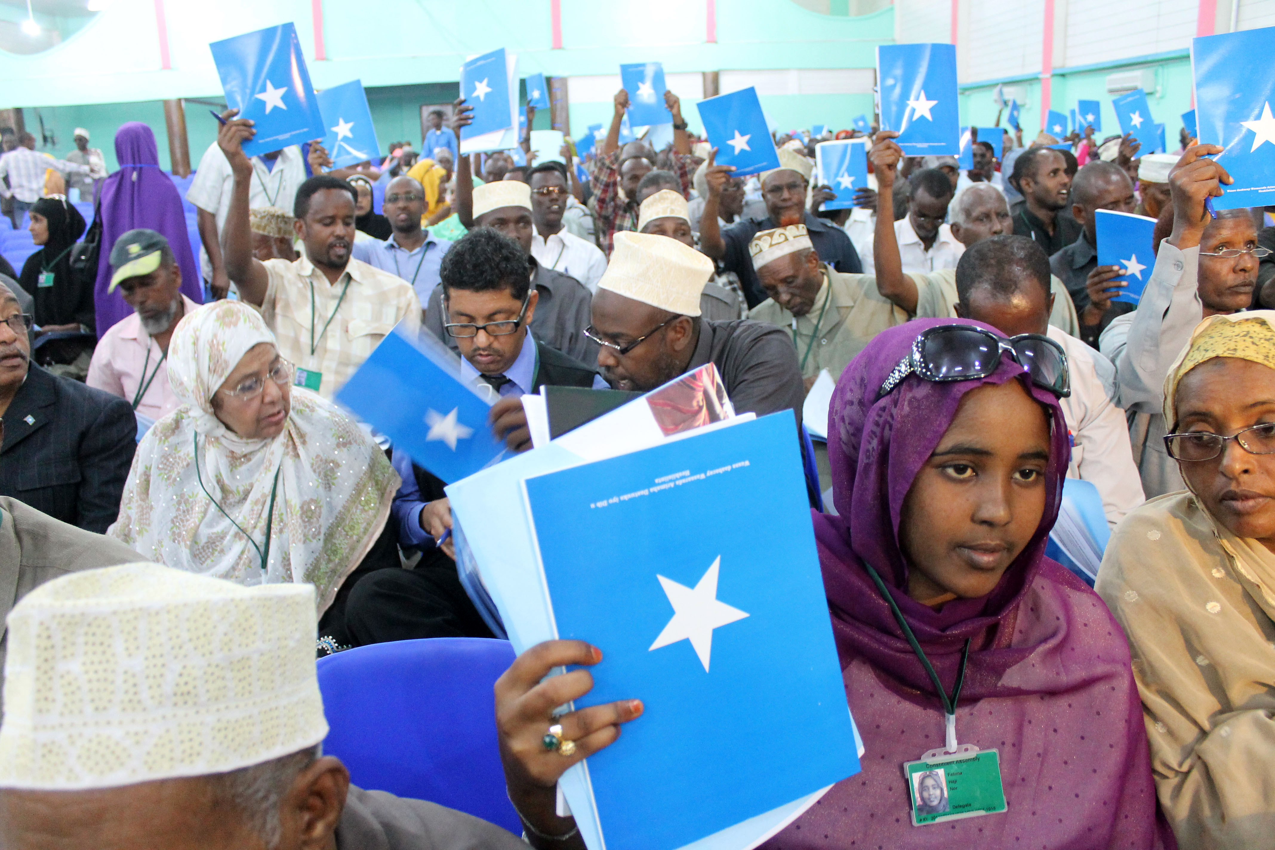 Somali delegates hold up the book of the