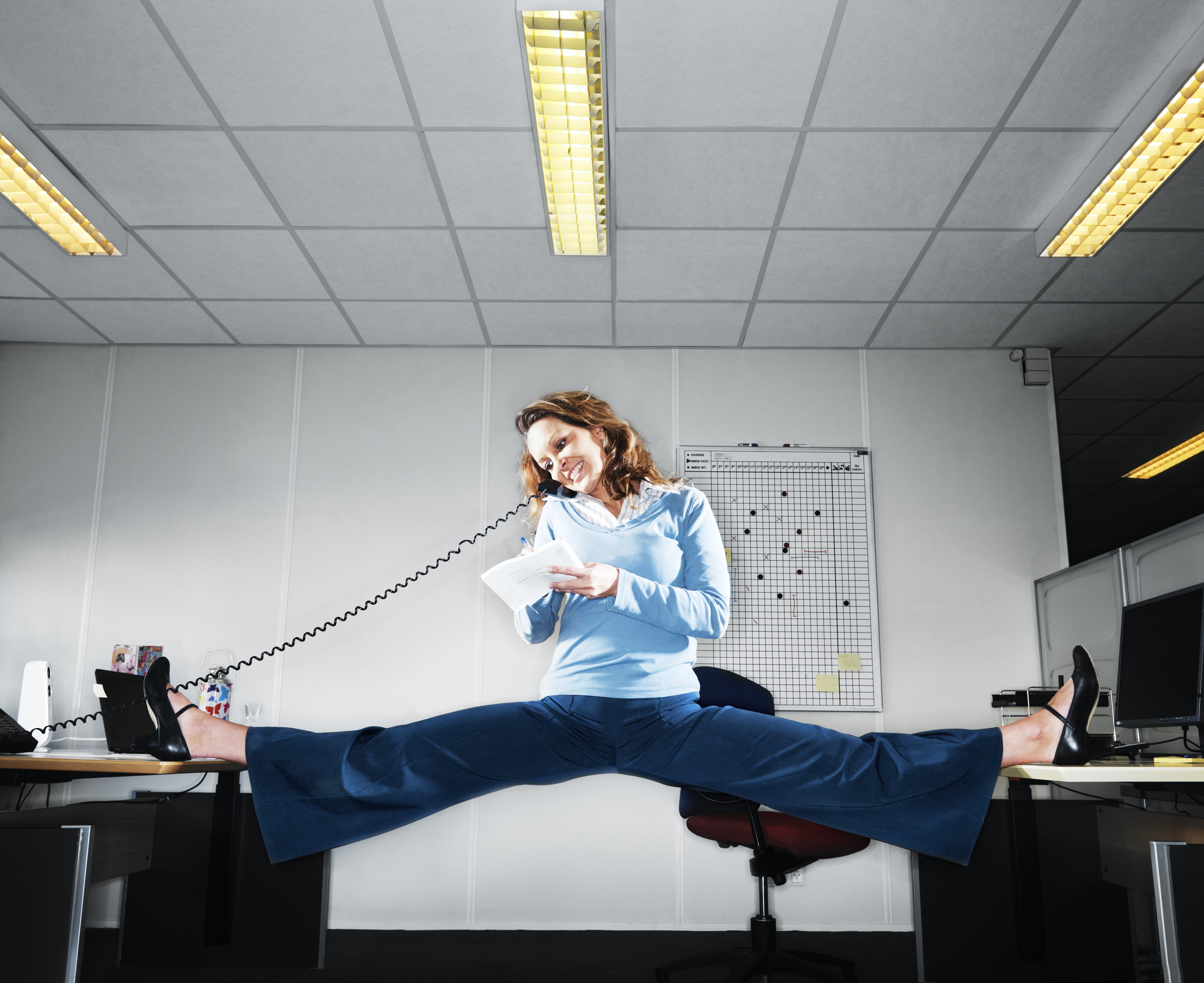 Woman talking on the phone doing the splits betwee