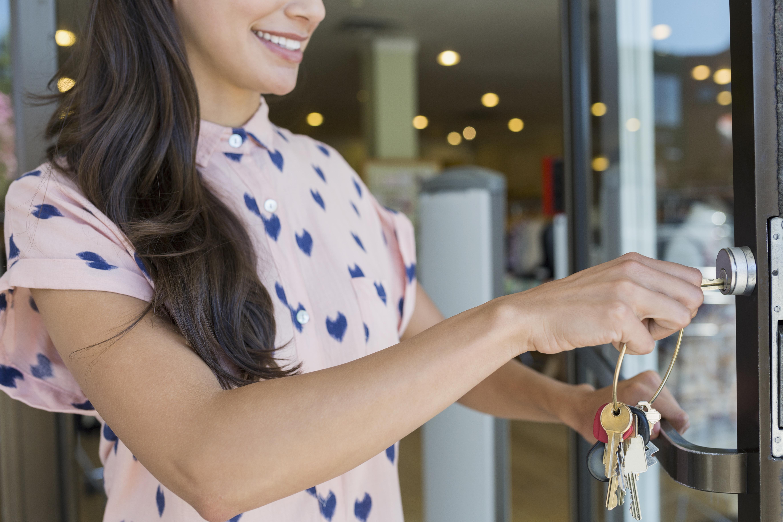 Business owner unlocking shop door with key