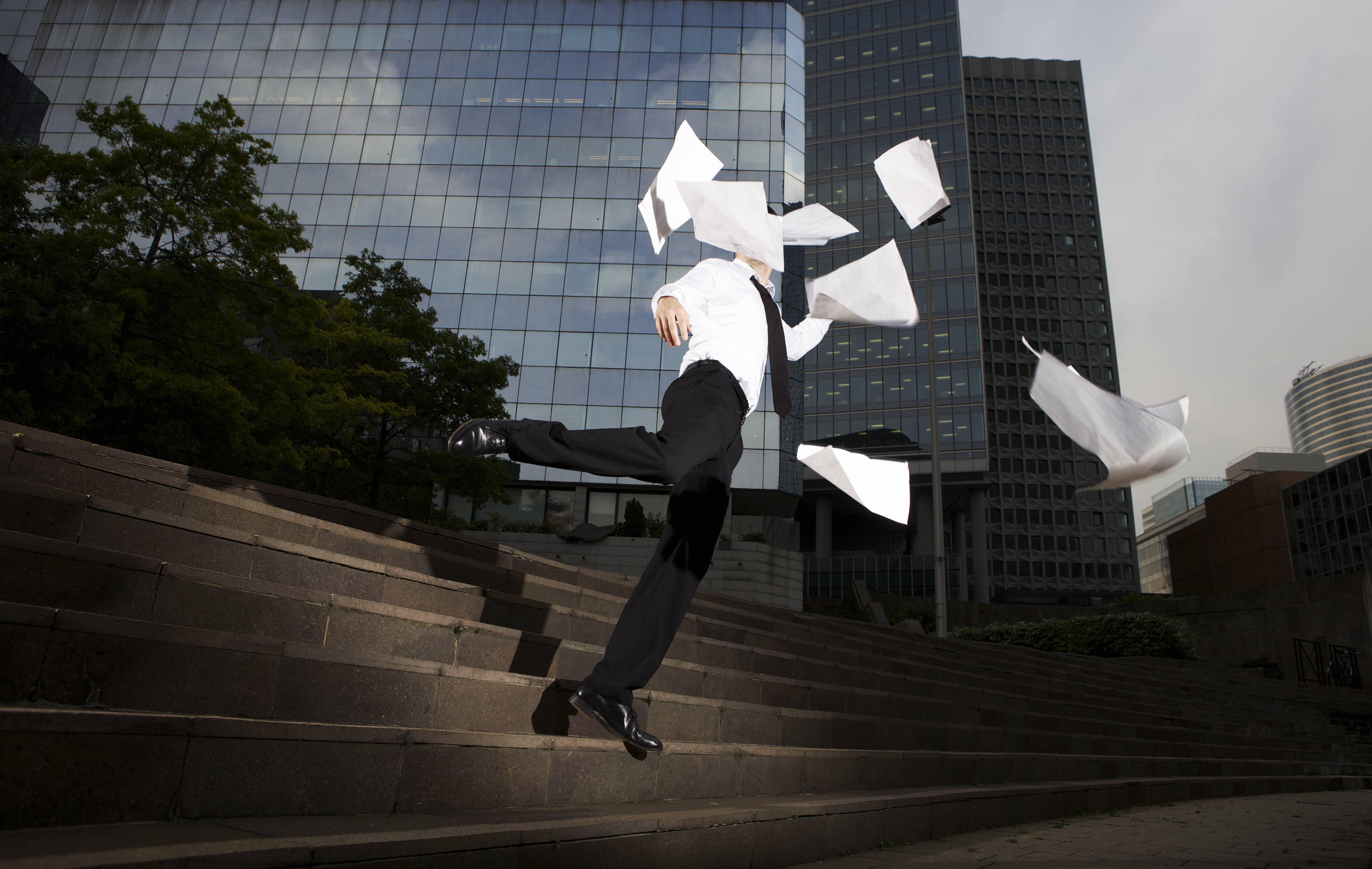 Businessman falling down steps with flying paper