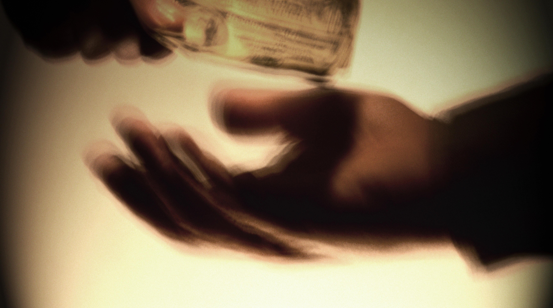 Two men exchanging money, close-up (digital enhancement)
