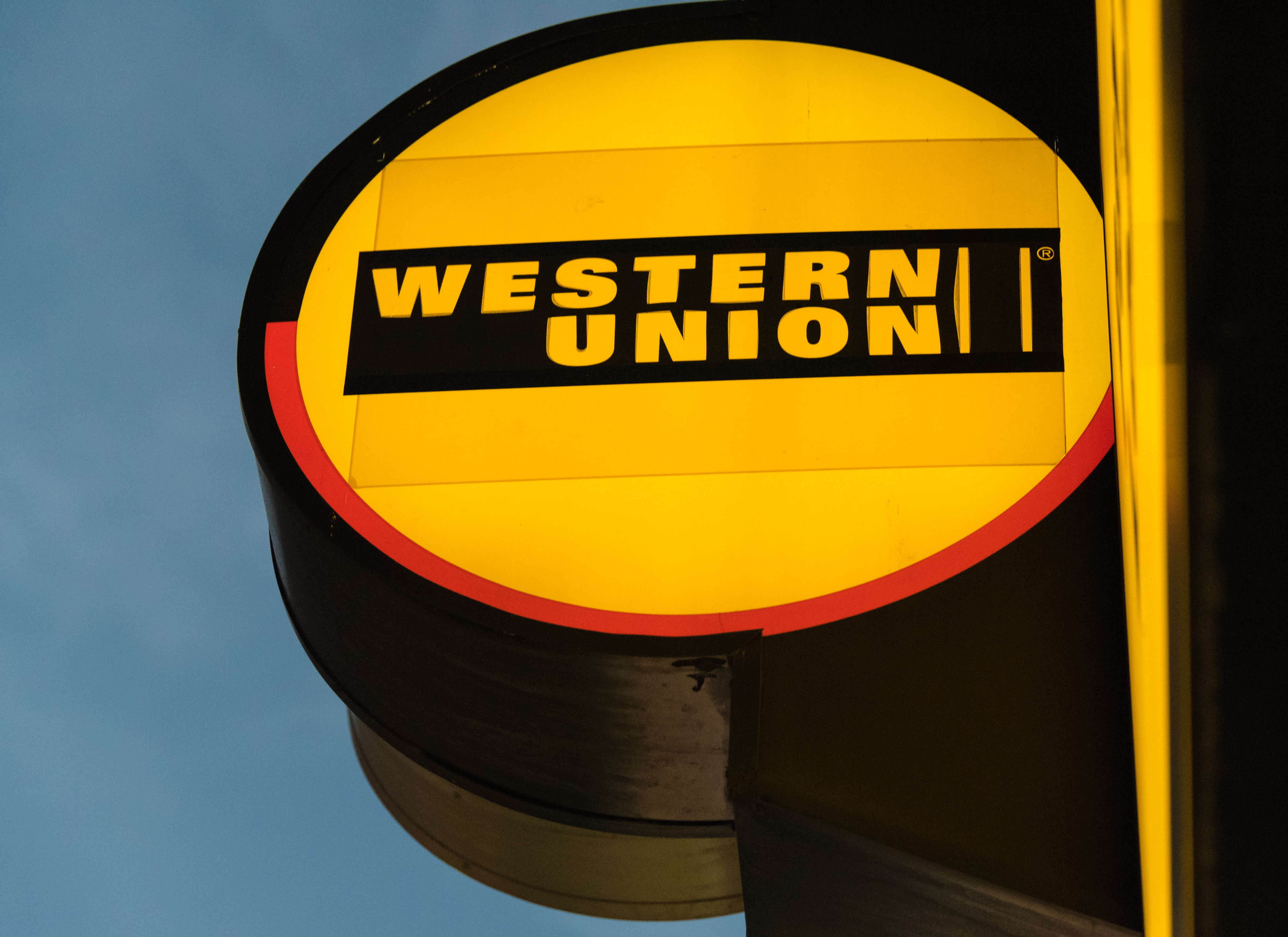The glowing signage of Western Union at its agent location