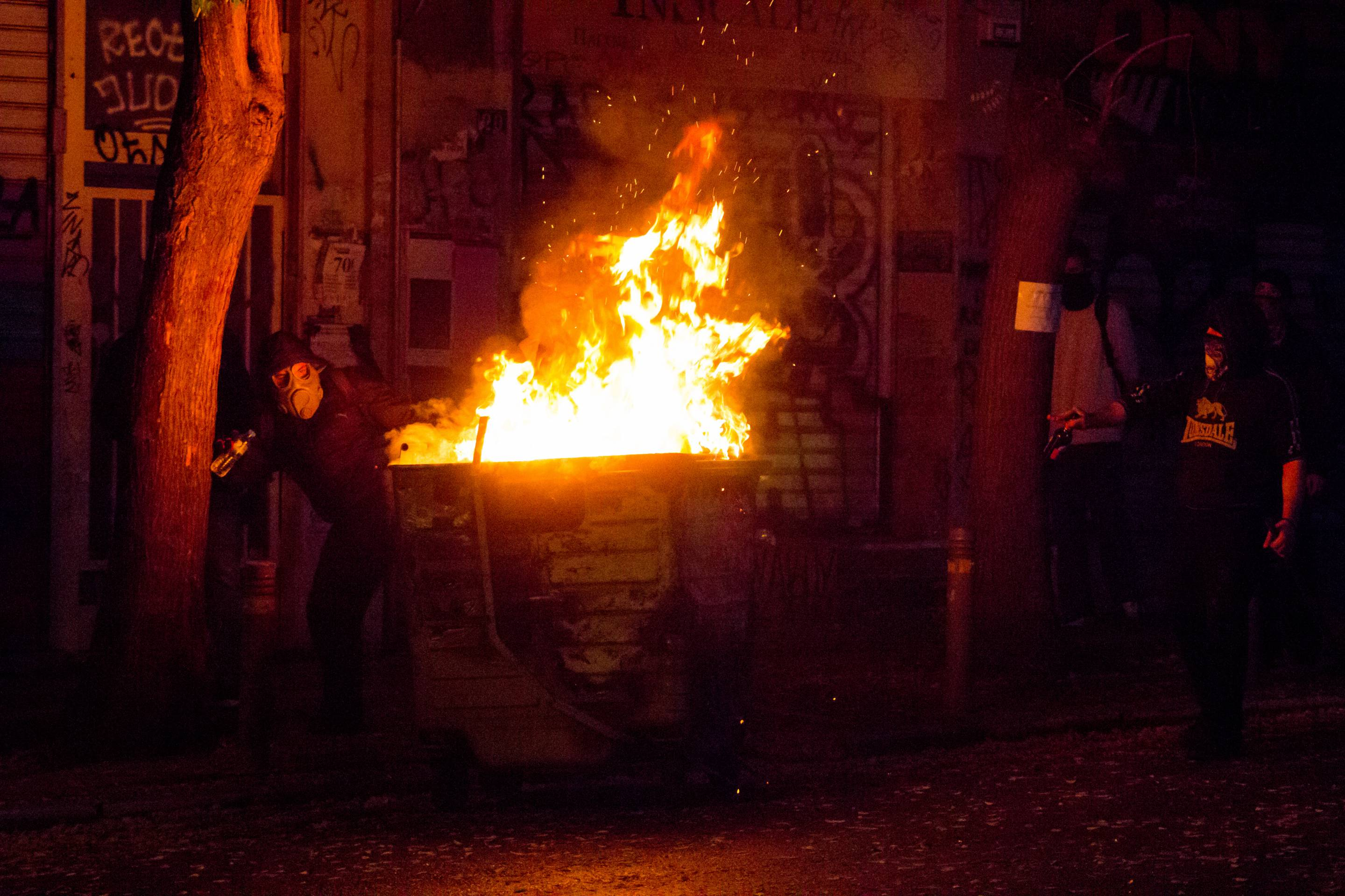 Rioters put a dumpster on fire to protect from tear gas