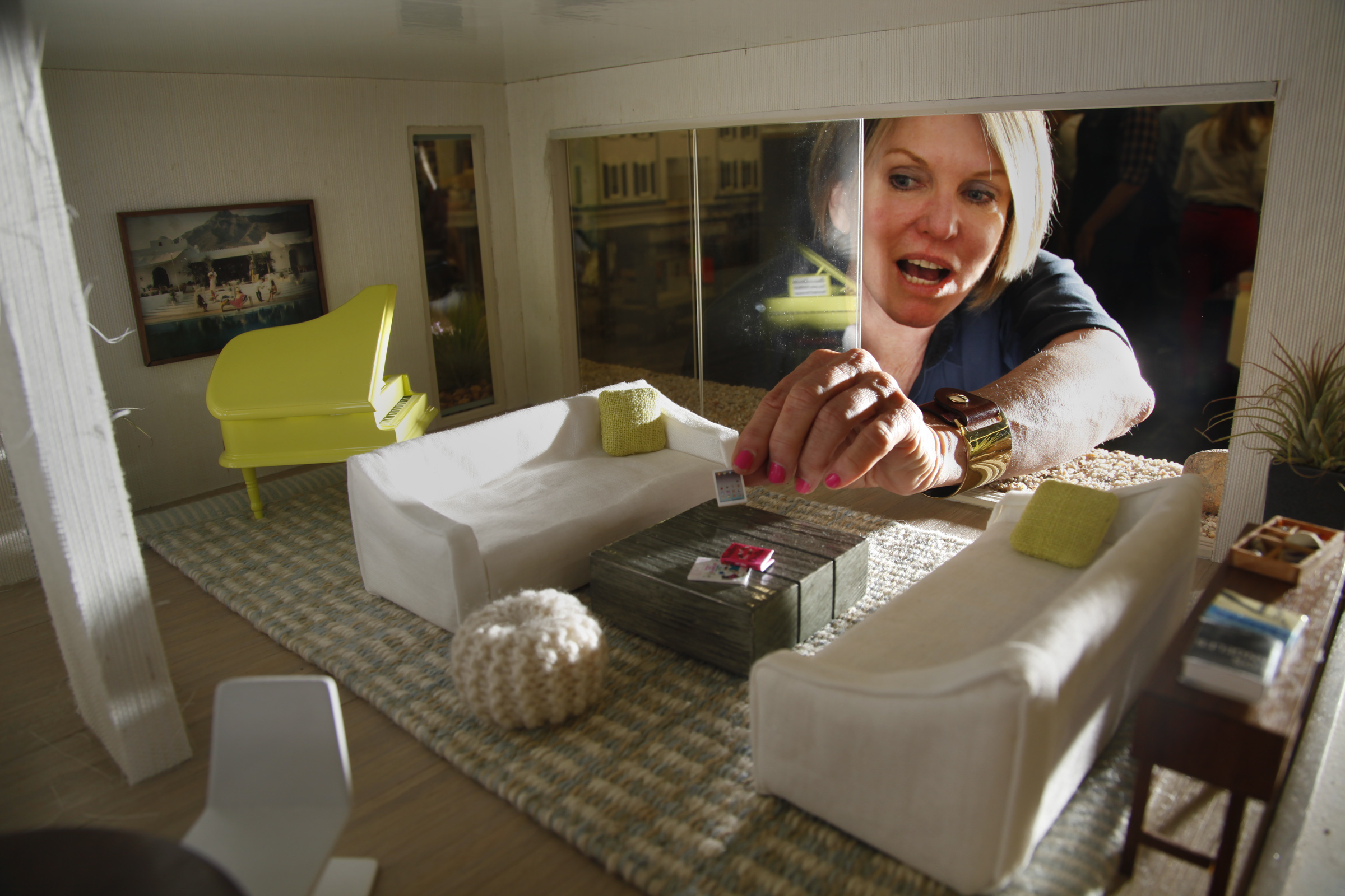 Interior designer Chris Barrett reaches through a sliding window wall in a contemporary beach dollh