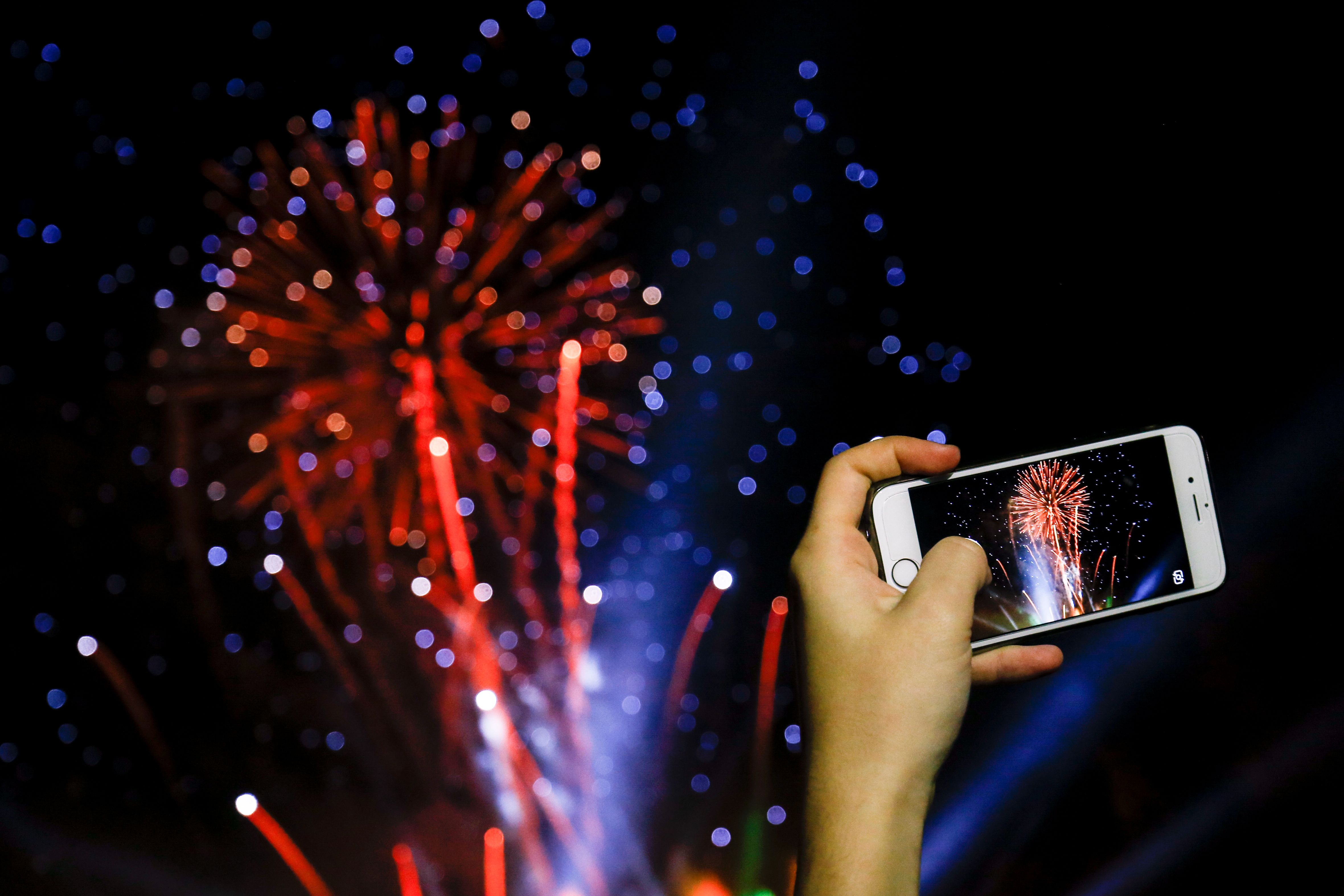 woman takes a picture with her smartphone of fireworks