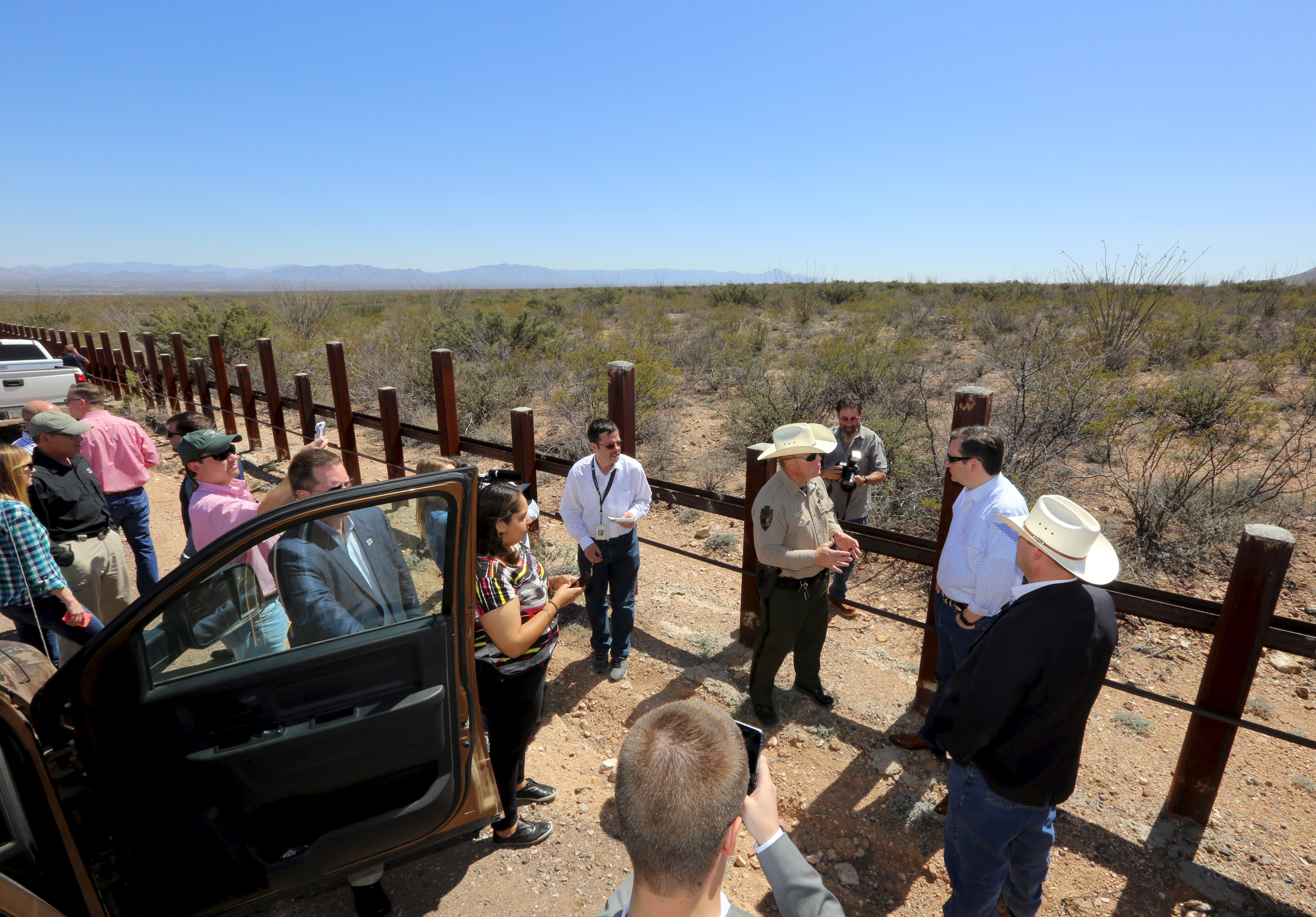 Republican Presidential candidate Ted Cruz stands along the United States border with Mexico as he speaks to Cochise County Sheriff Mark Dannels and Arizona State representative David Gowan near Douglas, Arizona
