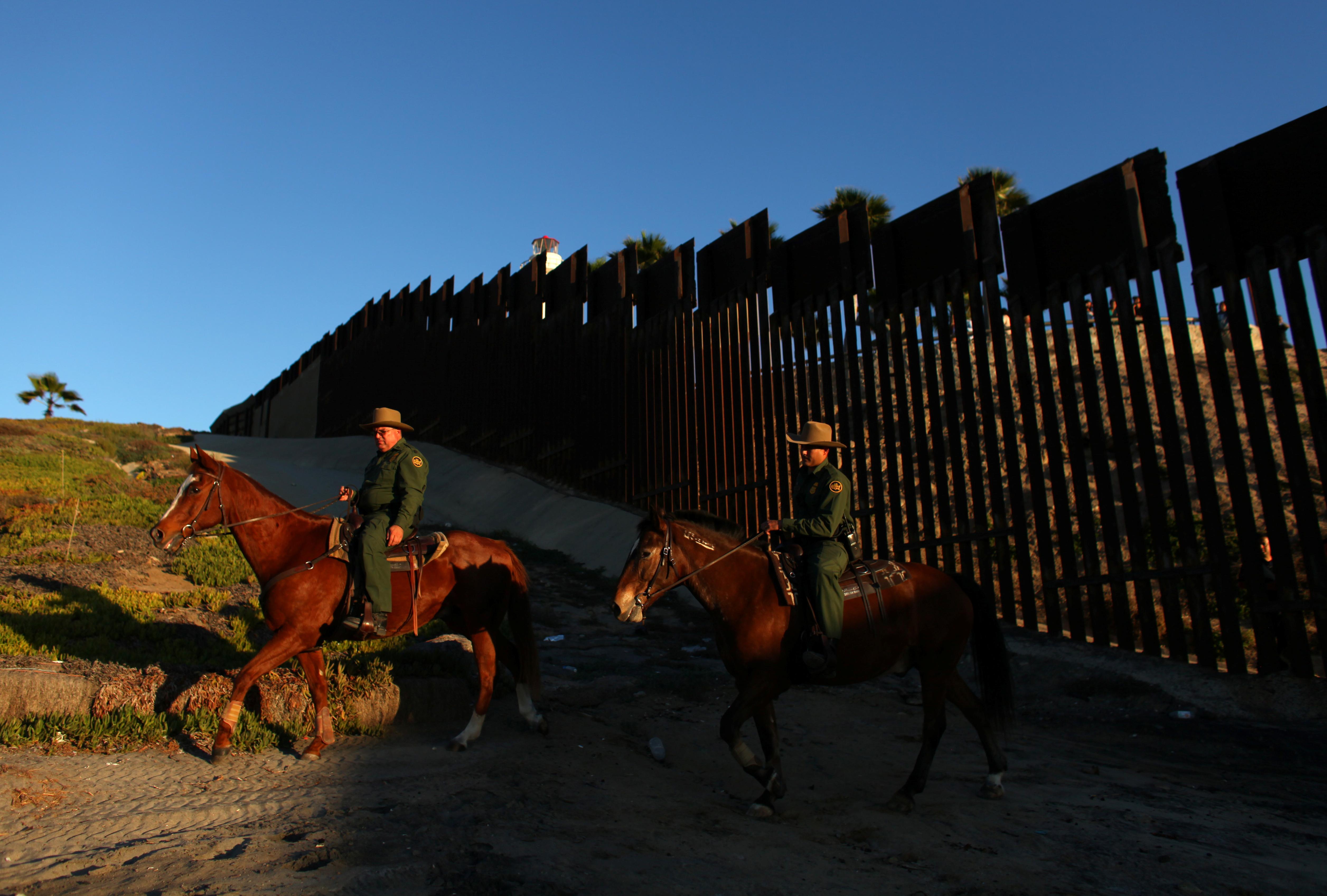 File Photo: U.S. border patrol agents on horseback patrol along the U.S. Mexico border fence near San Diego, California