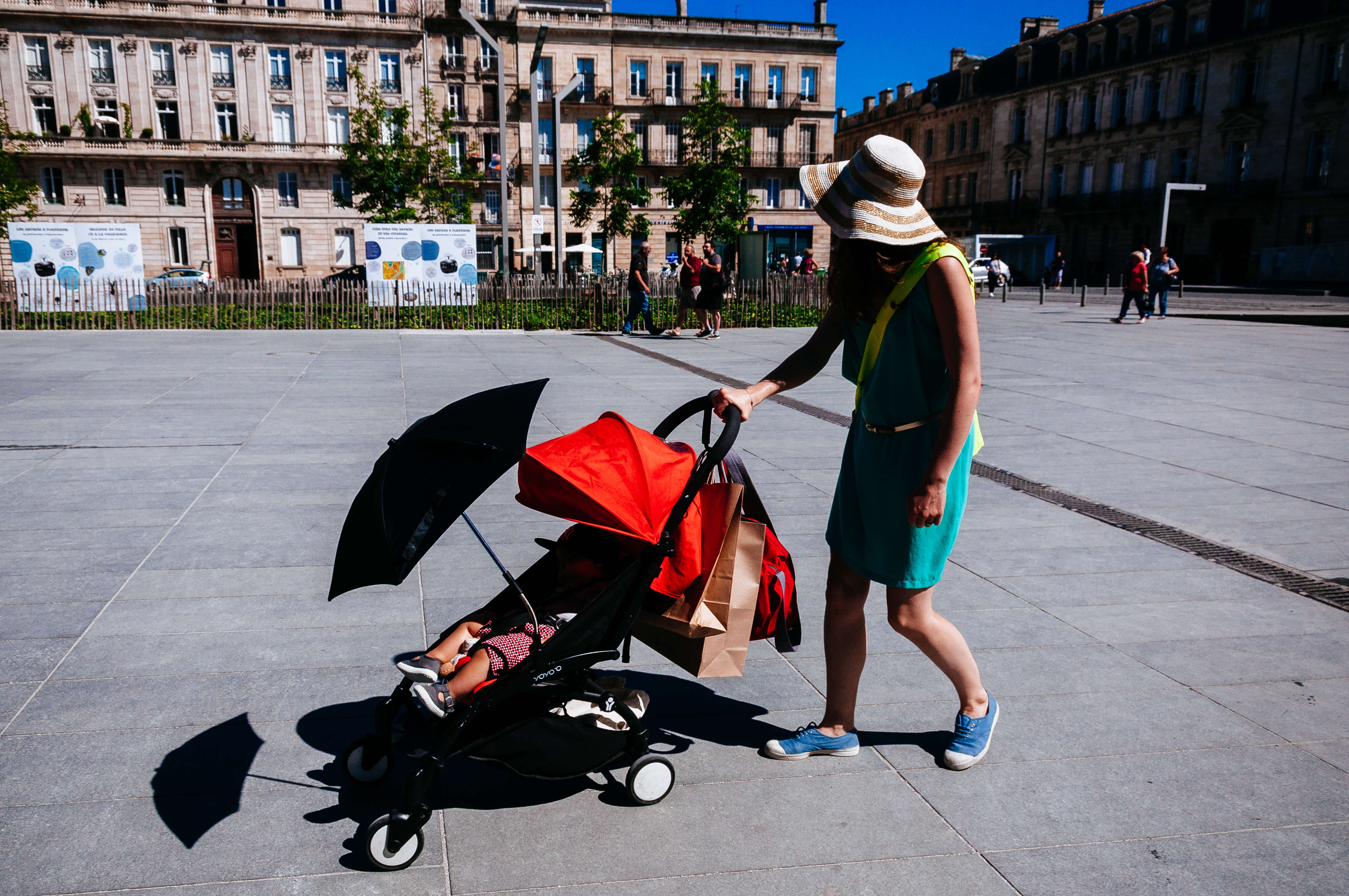 Woman pushing baby carriage on the street
