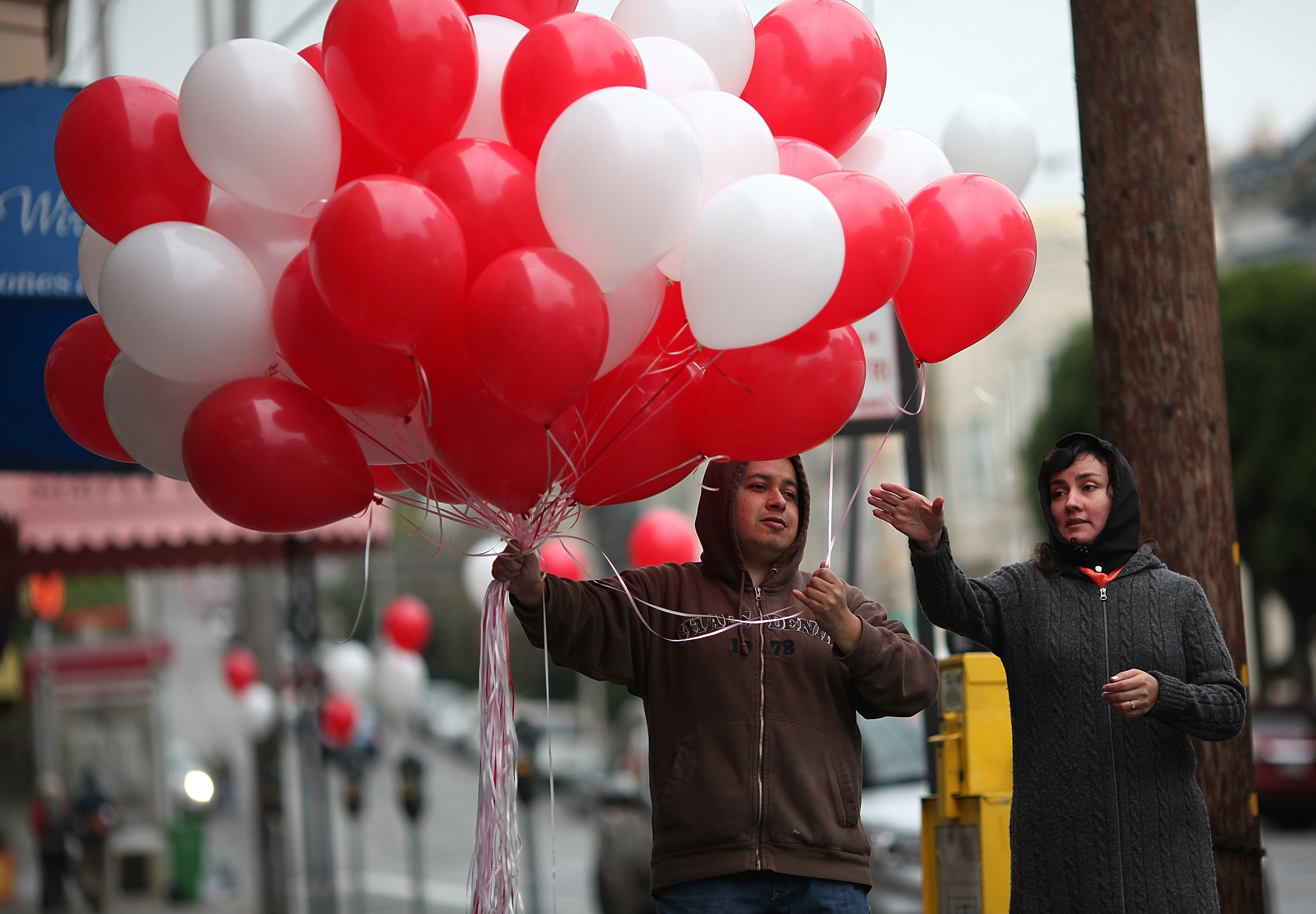 A man hands a balloon to a woman as he decorates Fillmore Street on Valentine's Day in San Francisco.