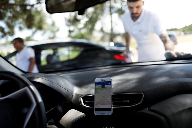 An Uber driver cleans his car as his cell phone shows the queue to pick up passengers departing Guarulhos International Airport in Sao Paulo