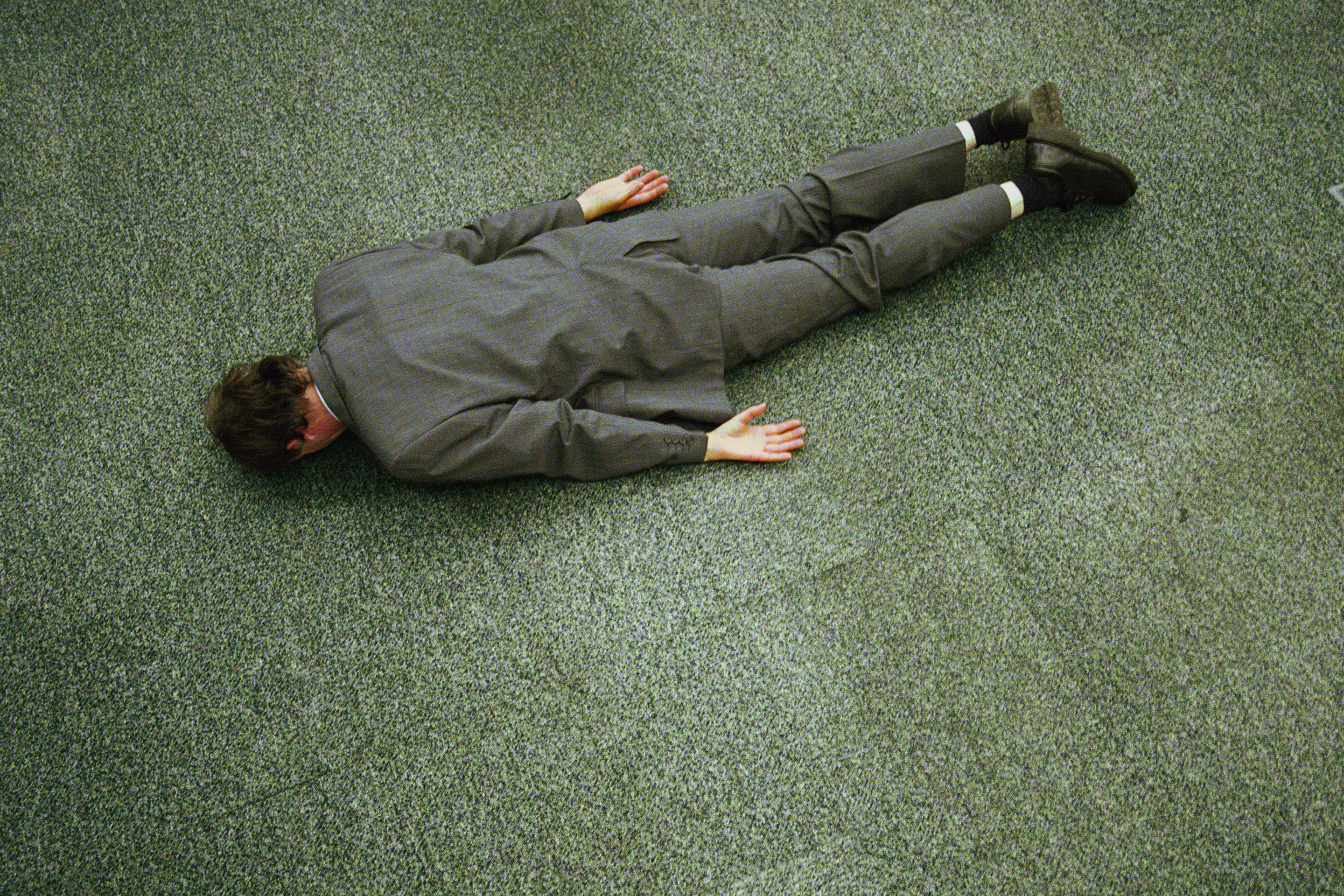 Businessman lying face down on floor, elevated view