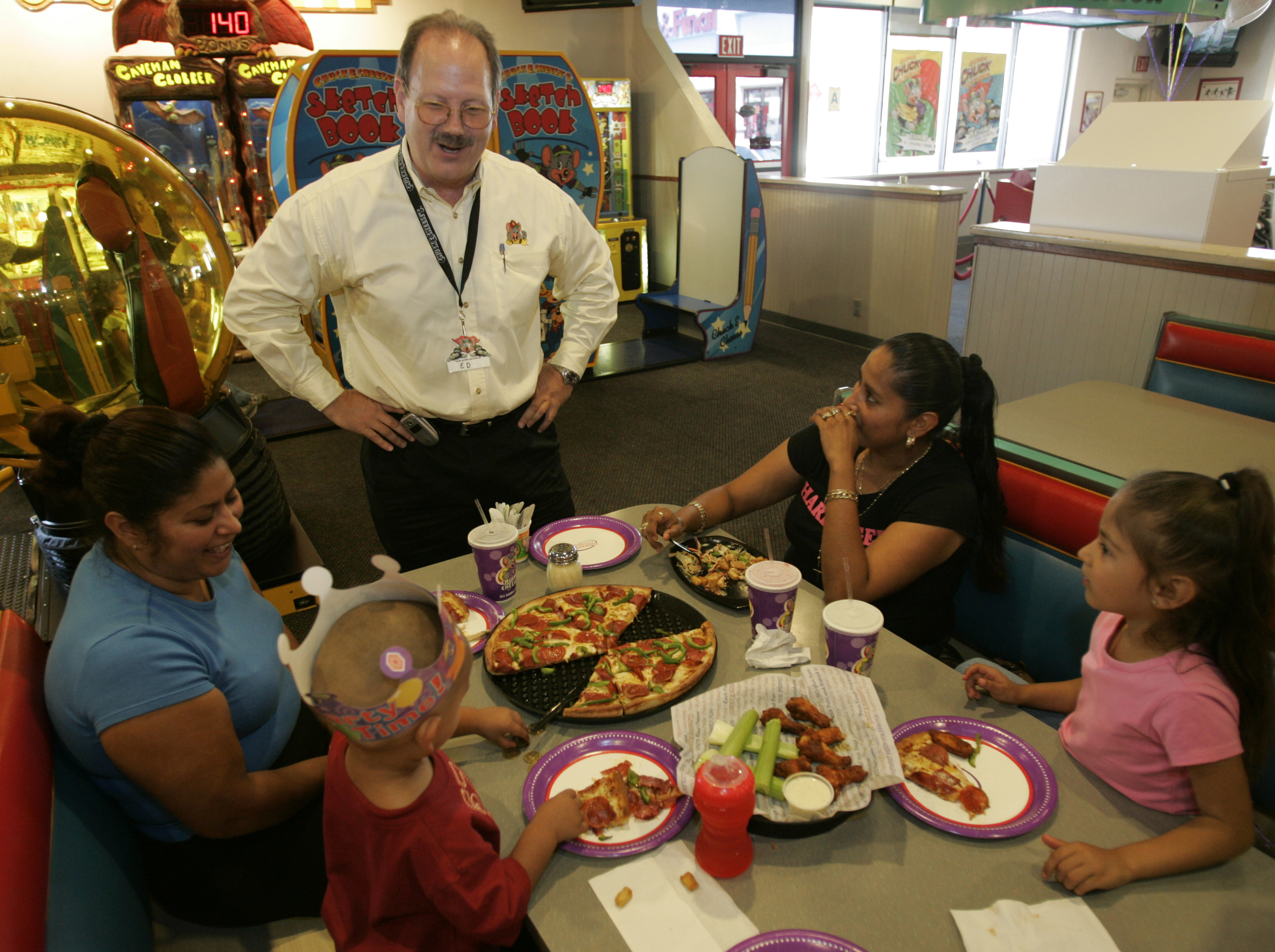 Ed Porter, Area Director for Chuck E. Cheese, chats with a family having a birthday party. This sto