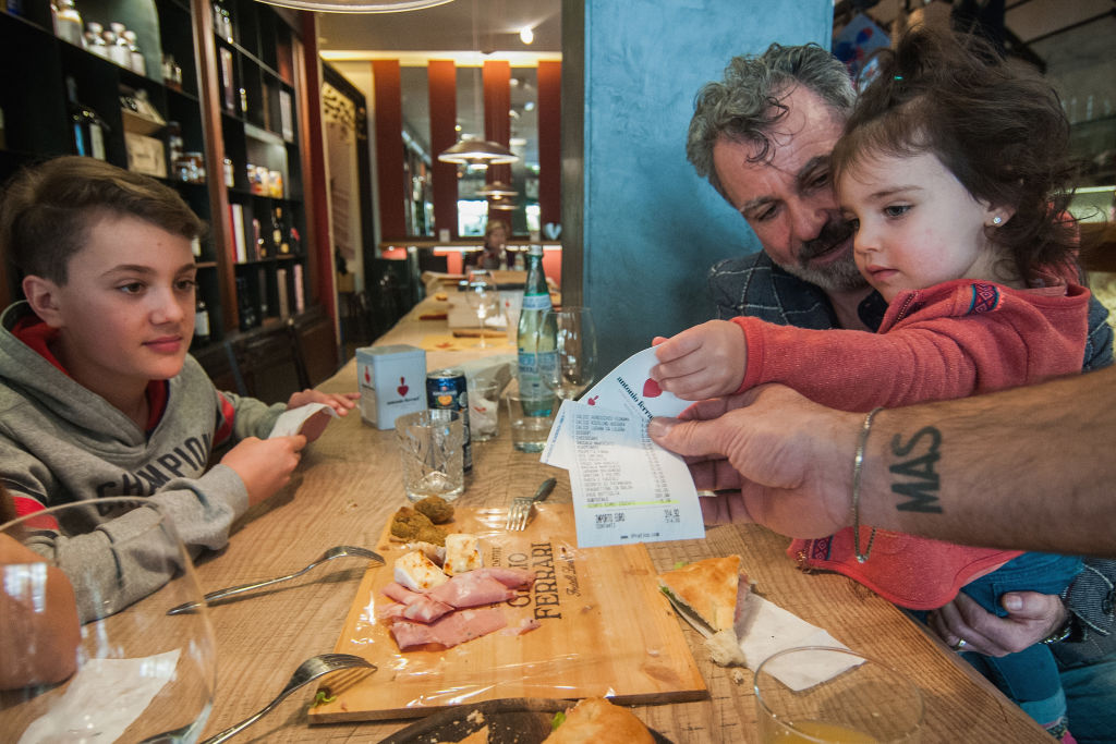 A family receives the bill with the 5% discount for the kids' good behavior in the Antonio Ferrari restaurant on Feb. 15, 2017, in Padua, Italy.
