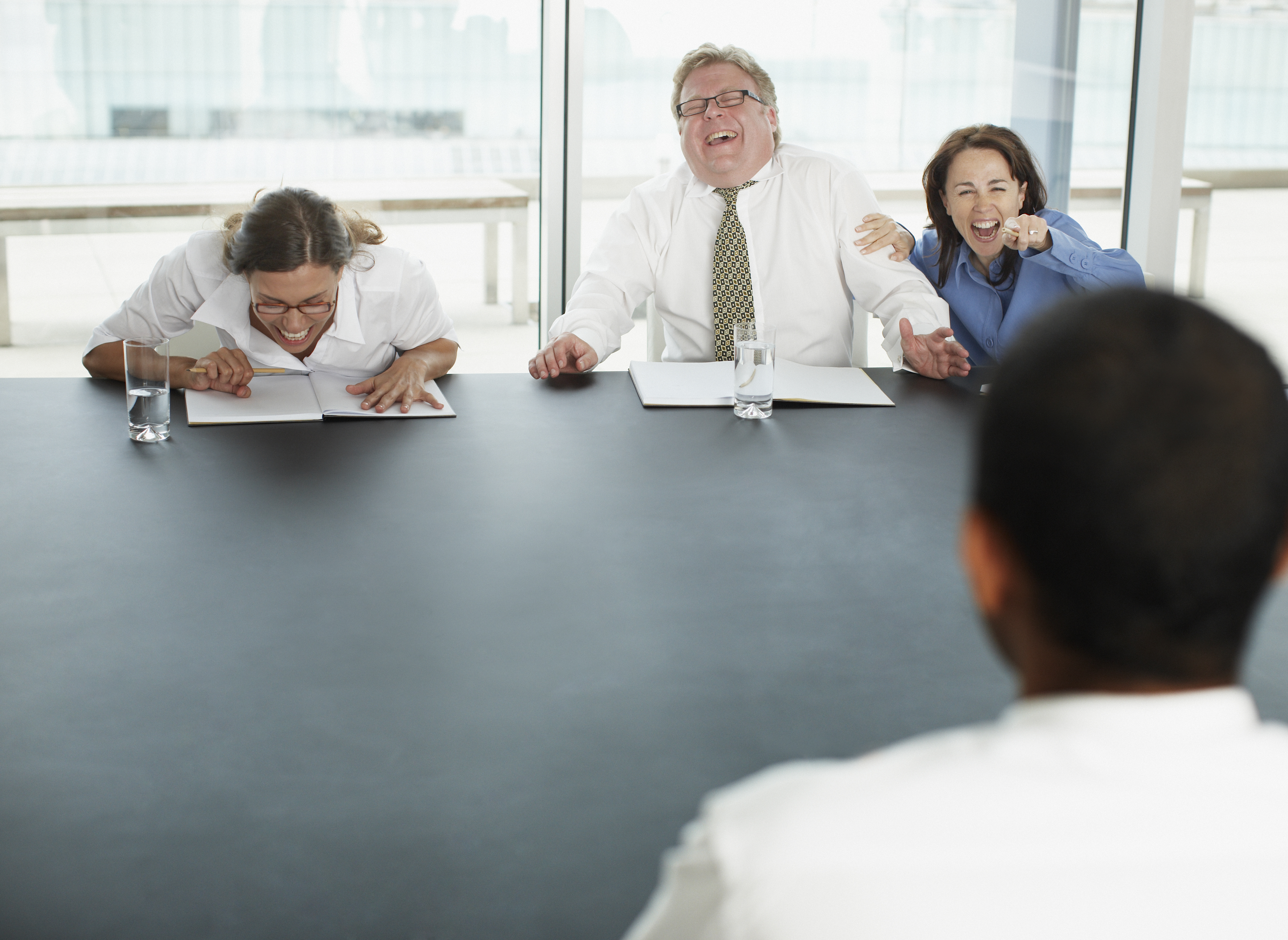 Businesspeople laughing at applicant in interview