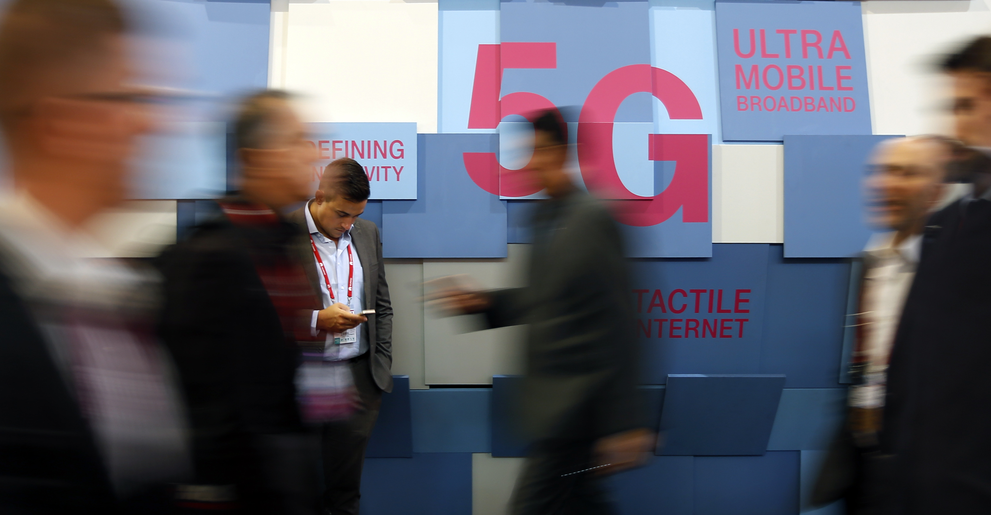 People walk past a 5G banner during the Mobile World Congress in Barcelona