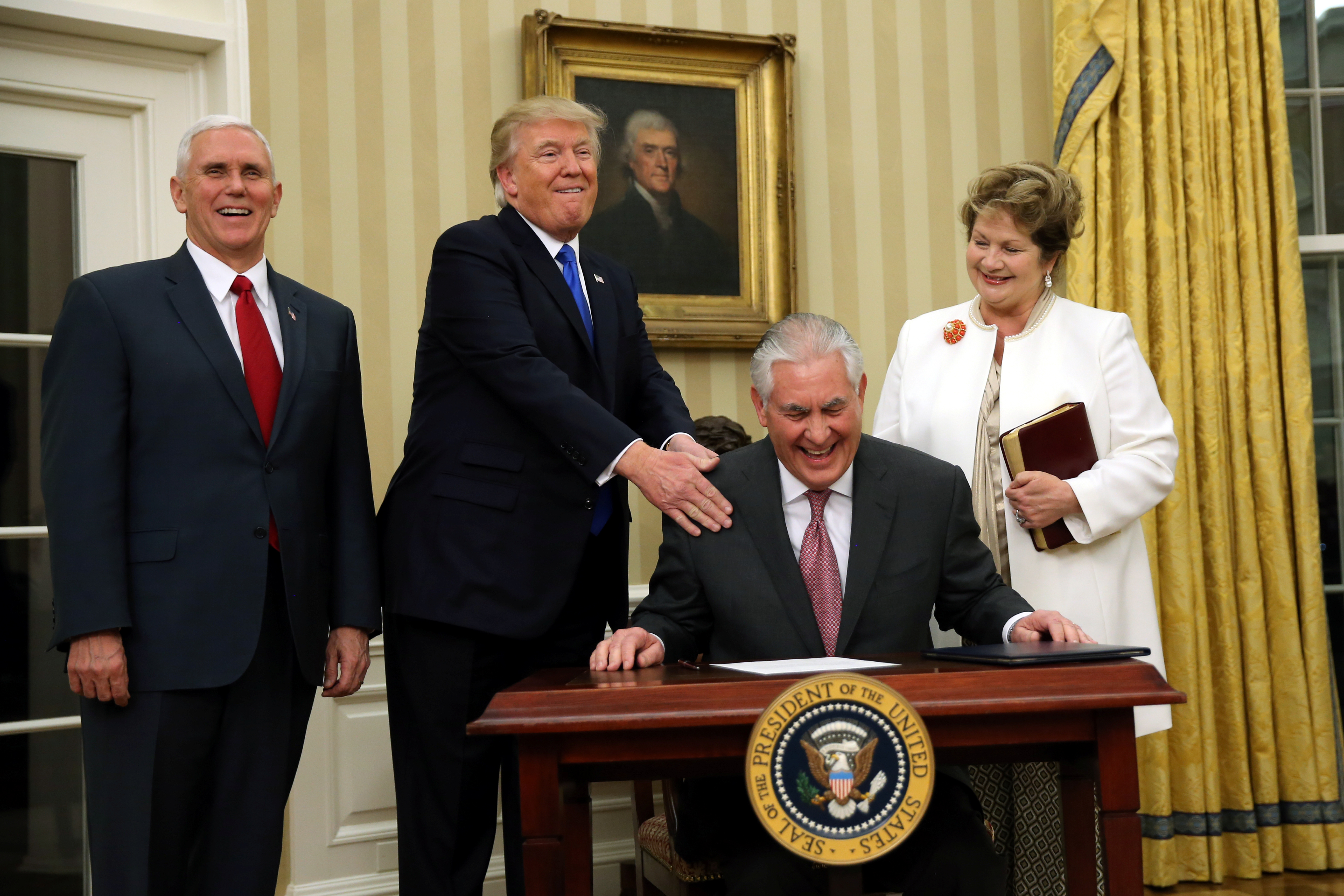 U.S. President Donald Trump reacts during the swearing in ceremony for new U.S. Secretary of State Rex Tillerson, accompanied by his wife Renda St. Clair and Vice President Mike Pence at the Oval Office of the White House in Washington, DC