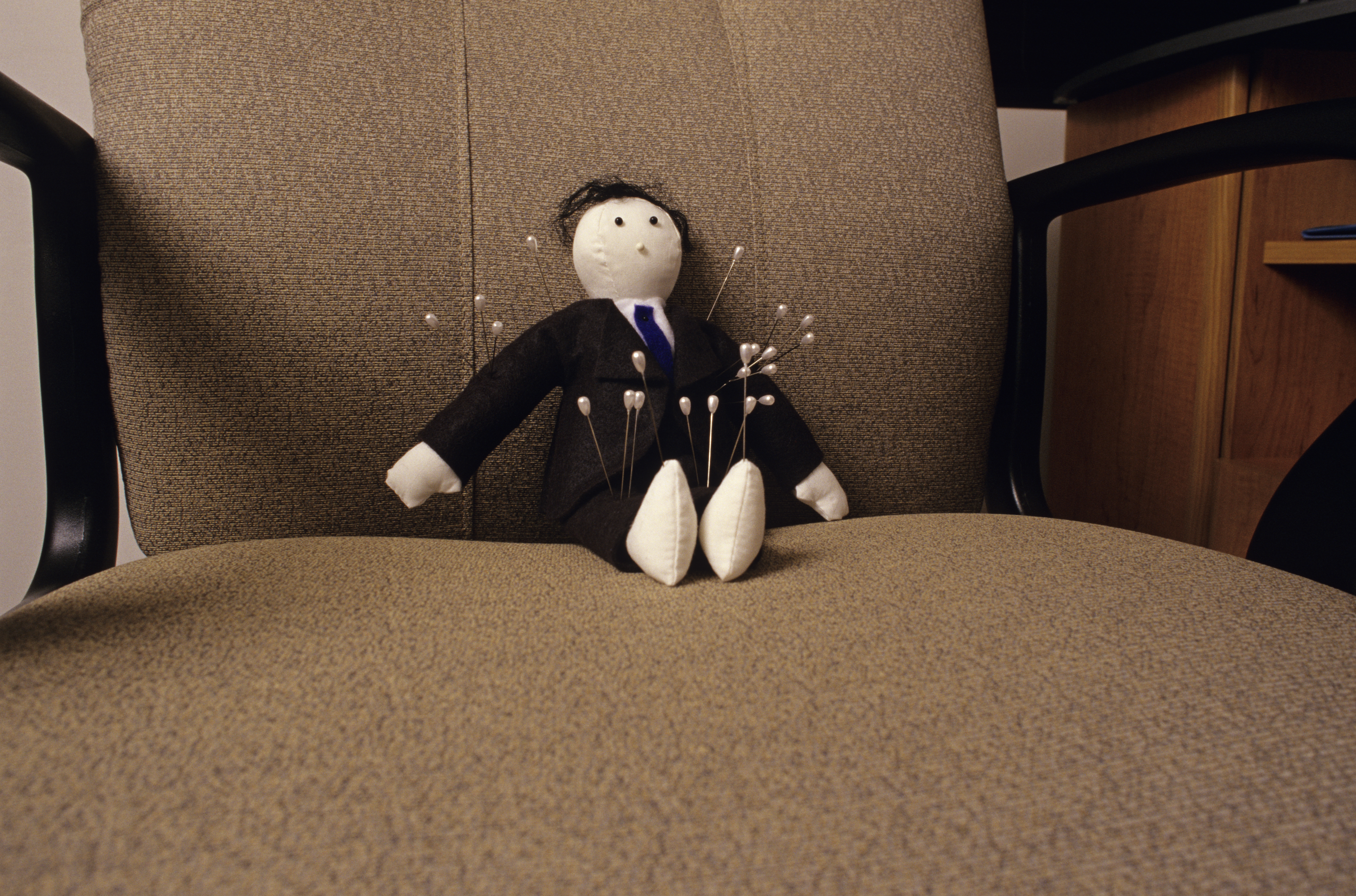 Voodoo doll sitting in chair in office