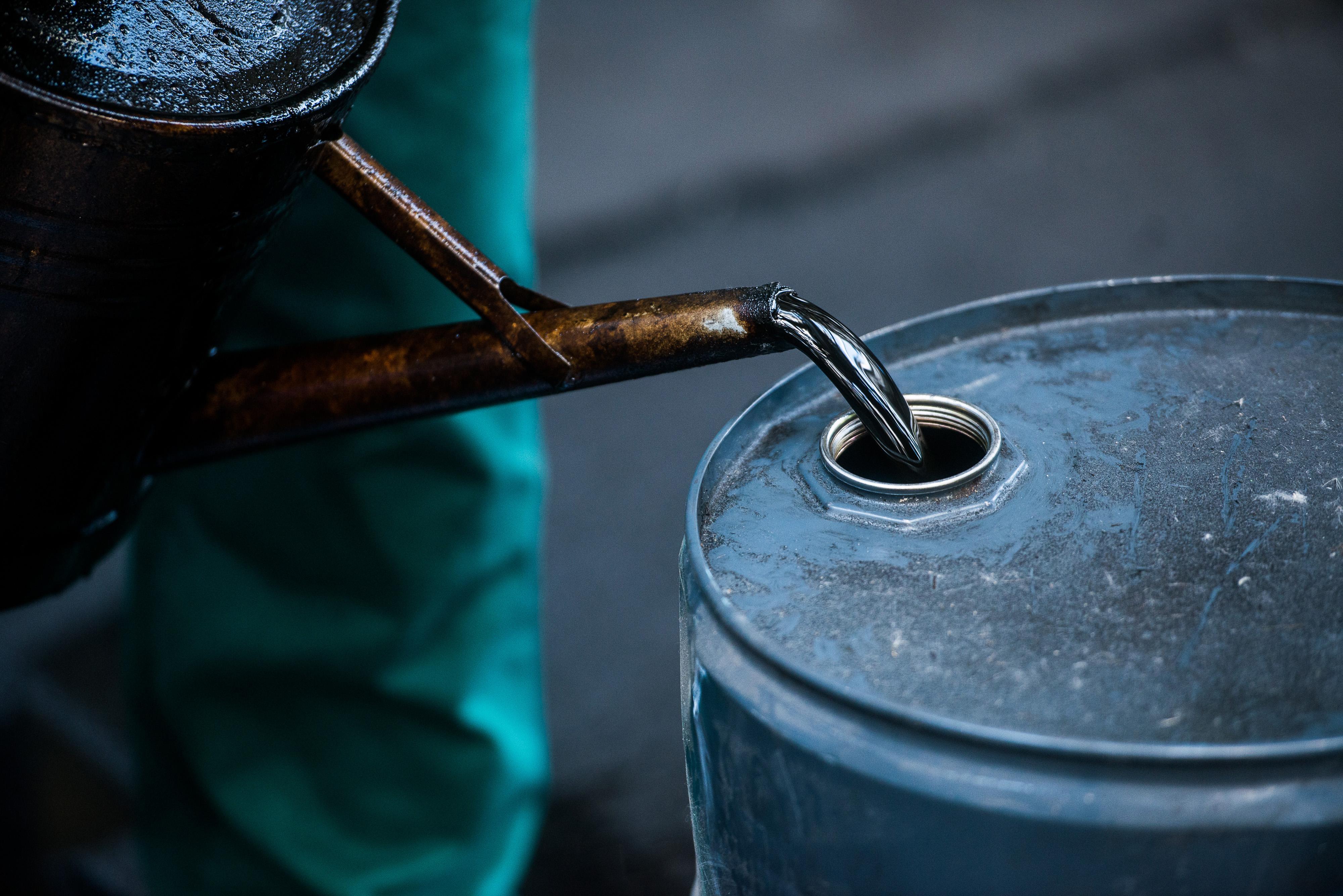 A worker pours liquid oil into a barrel.