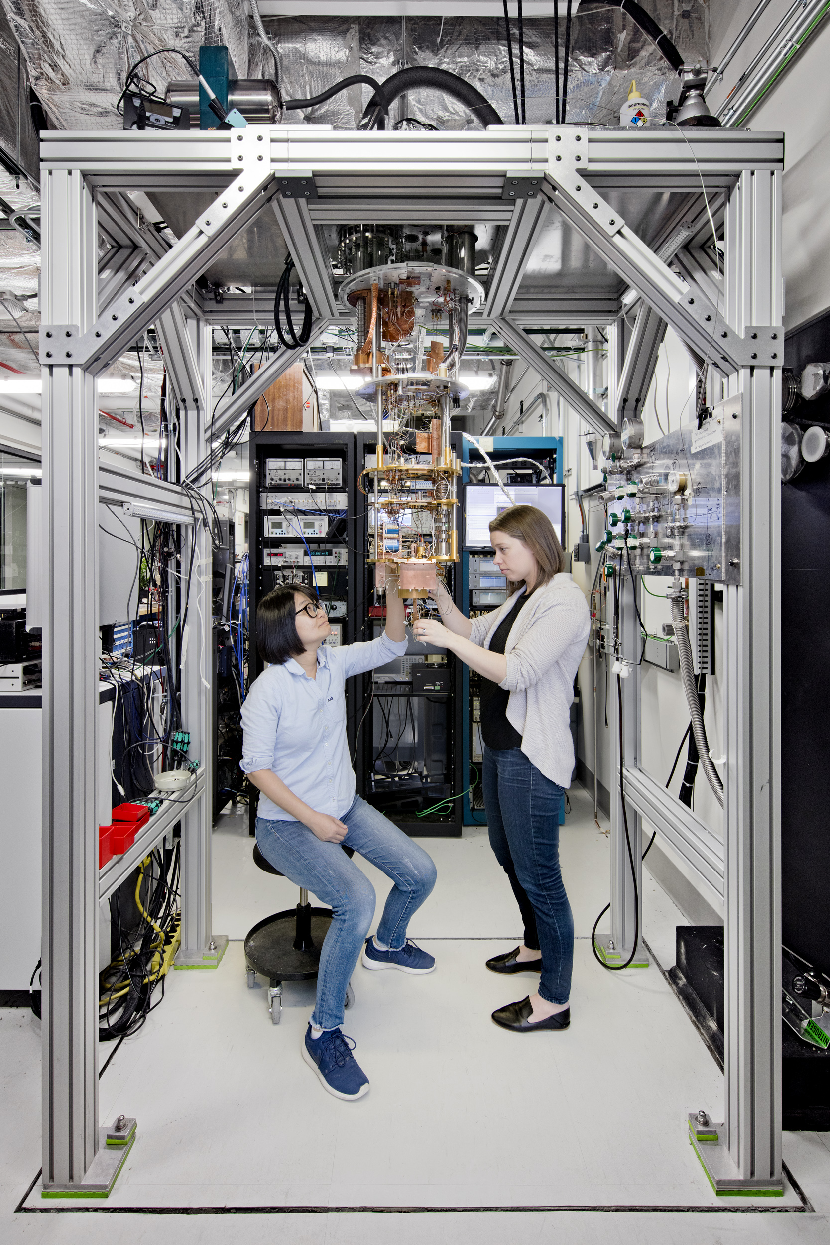 IBM Quantum Computing Scientists Hanhee Paik (left) and Sarah Sheldon (right) examine hardware inside an open dilution fridge at the IBM Q Lab at IBM's T. J. Watson Research Center in Yorktown, NY.