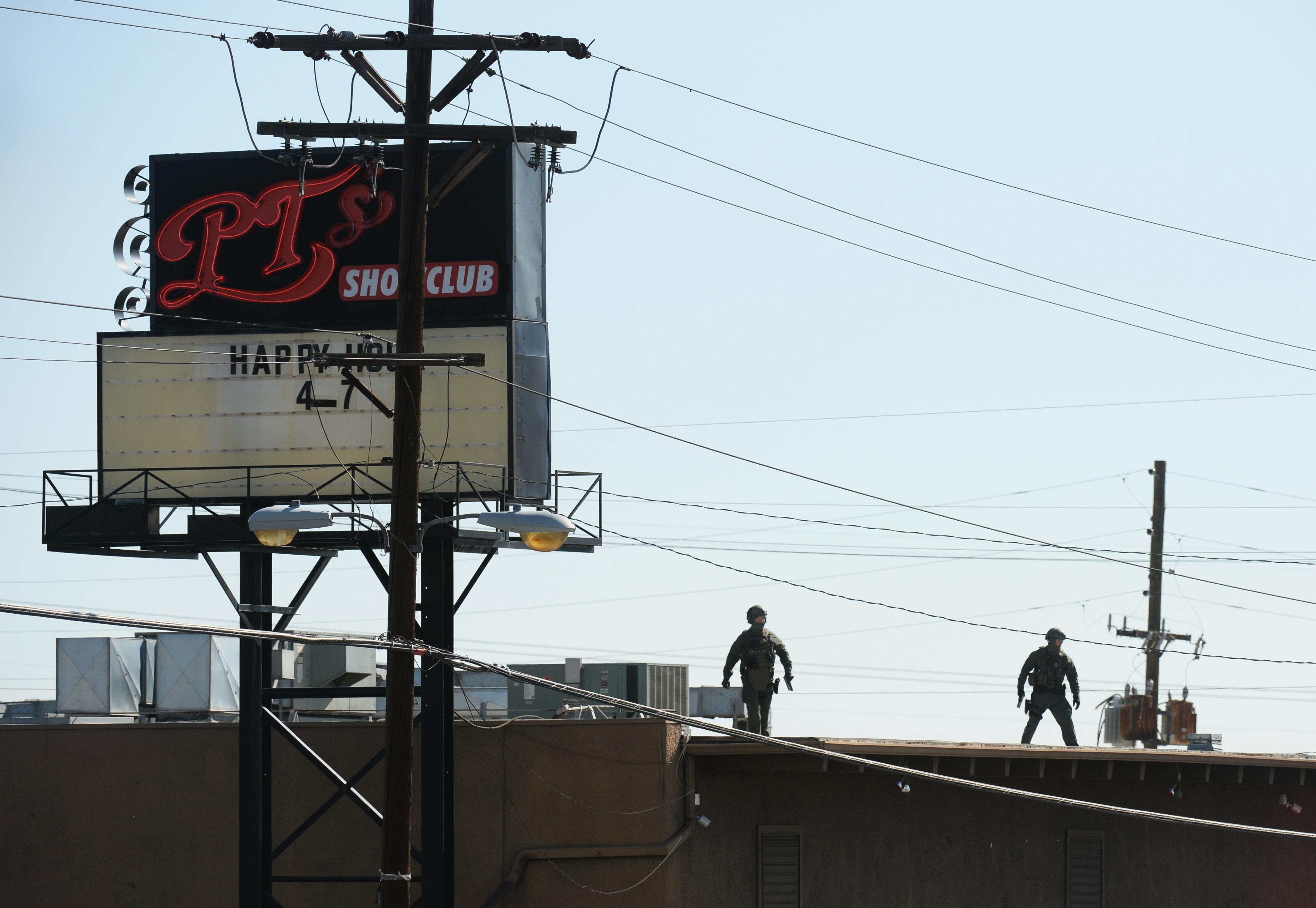 Denver police clear the scene outside of PT's Showclub