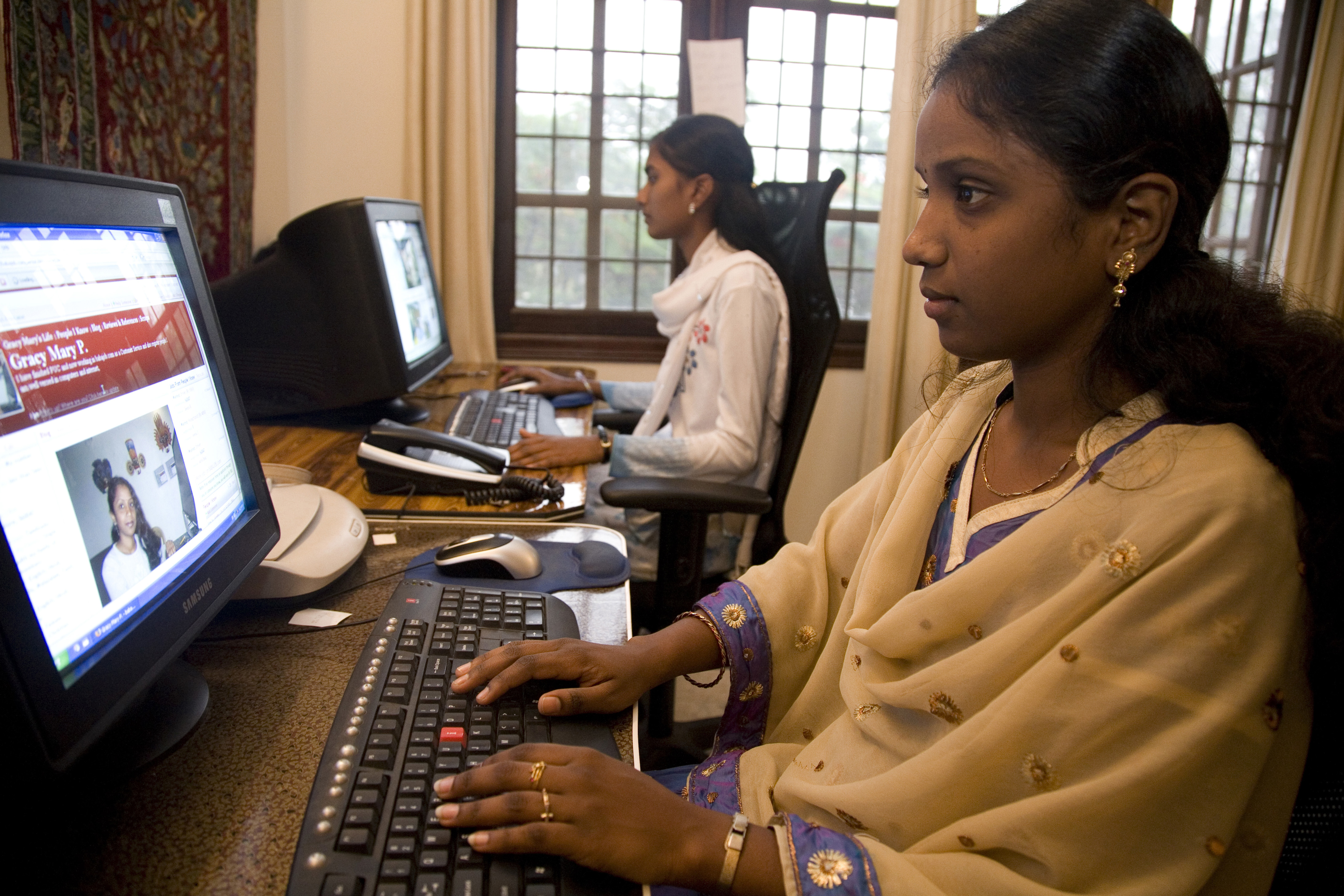 An employee in Bangalore works on her computer in a small office