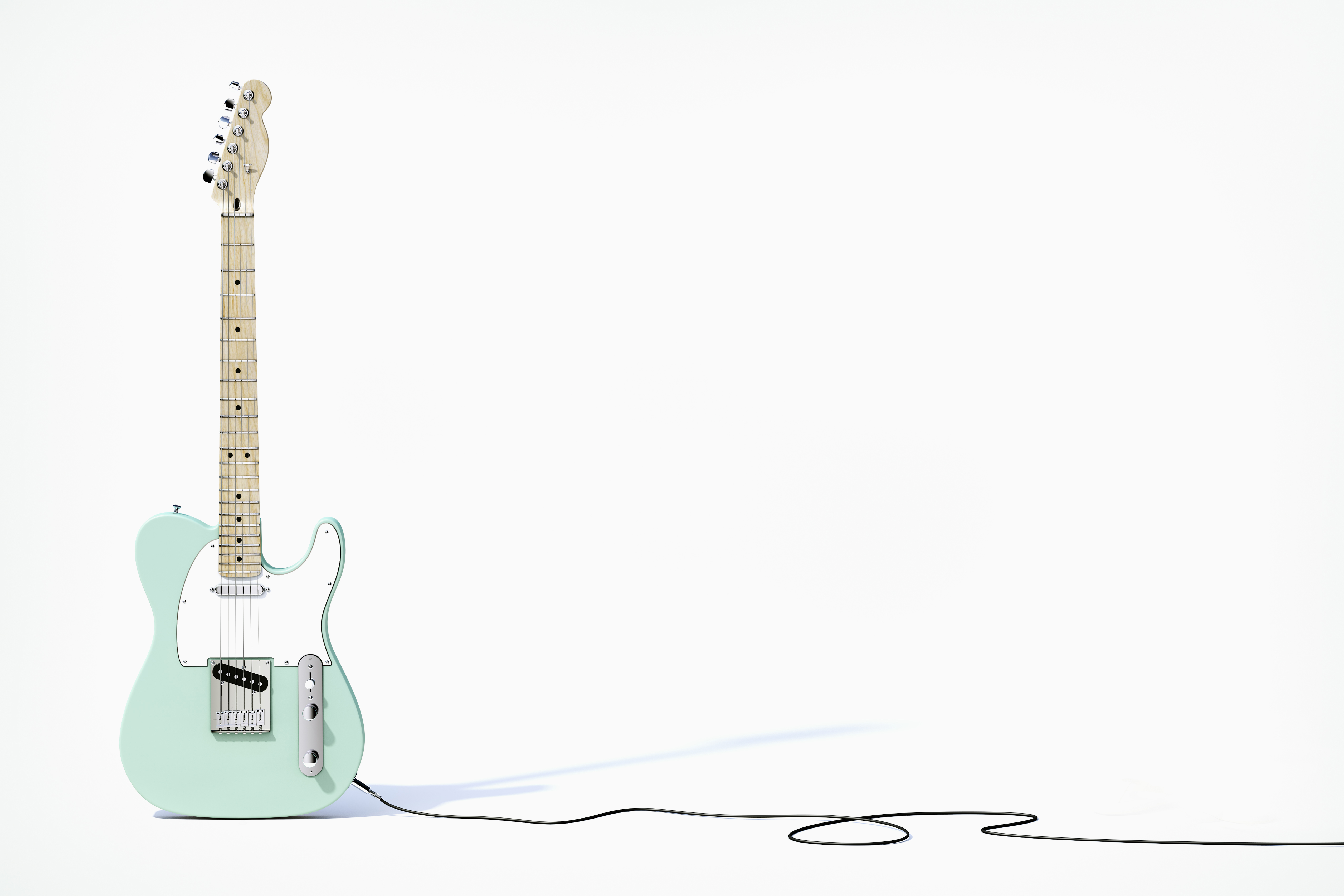 Green guitar balancing on white background