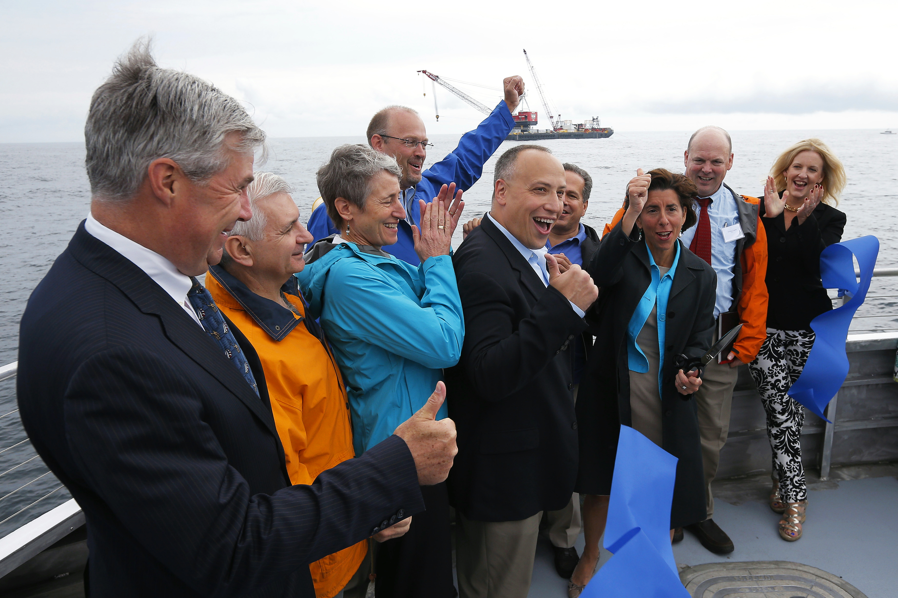 Elected officials and Deepwater Wind executives cheer during a ceremony to mark the installation of the first support jacket for a wind farm in the waters of the Atlantic Ocean off Block Island