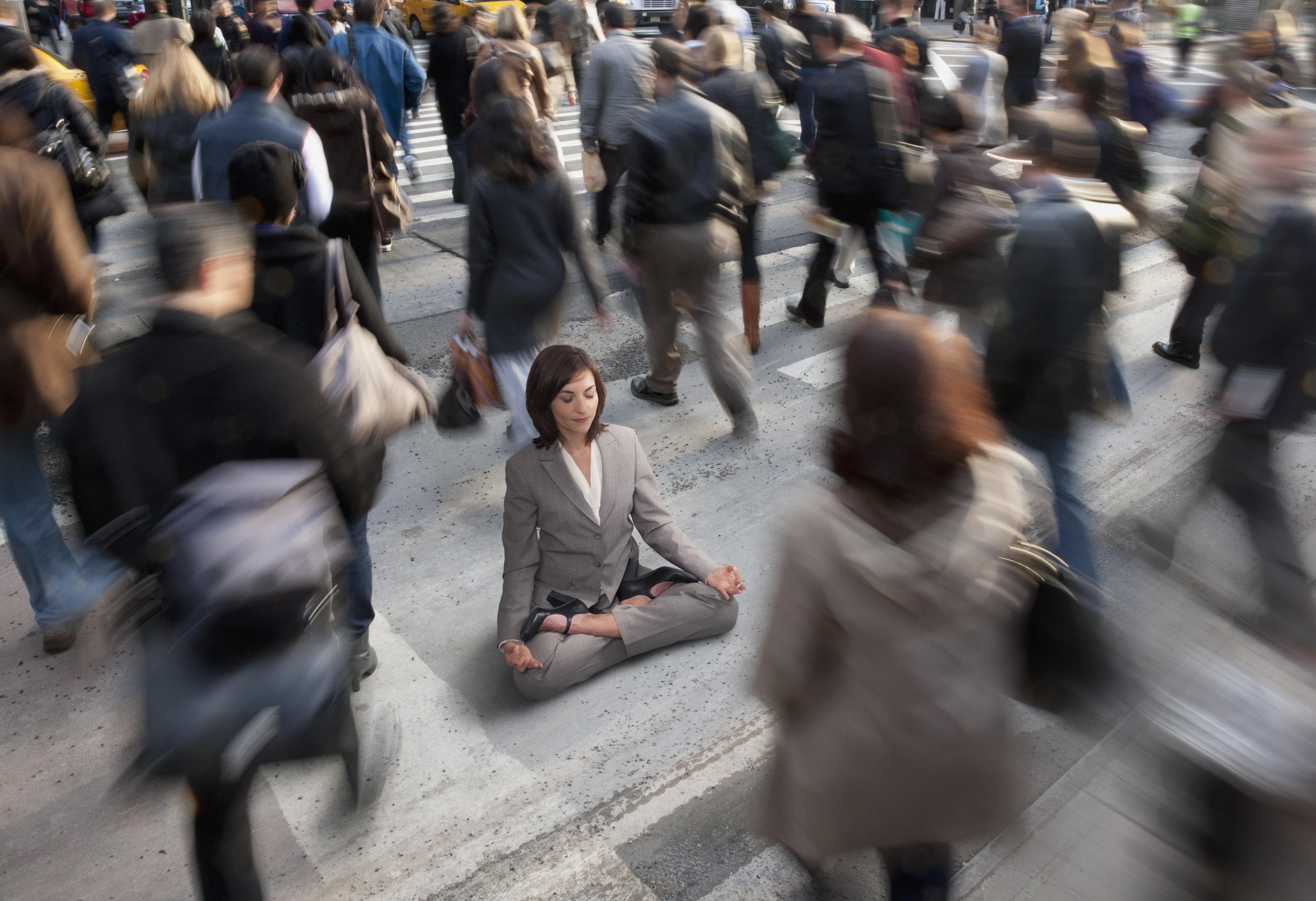 Businesswoman practicing yoga in busy urban crosswalk